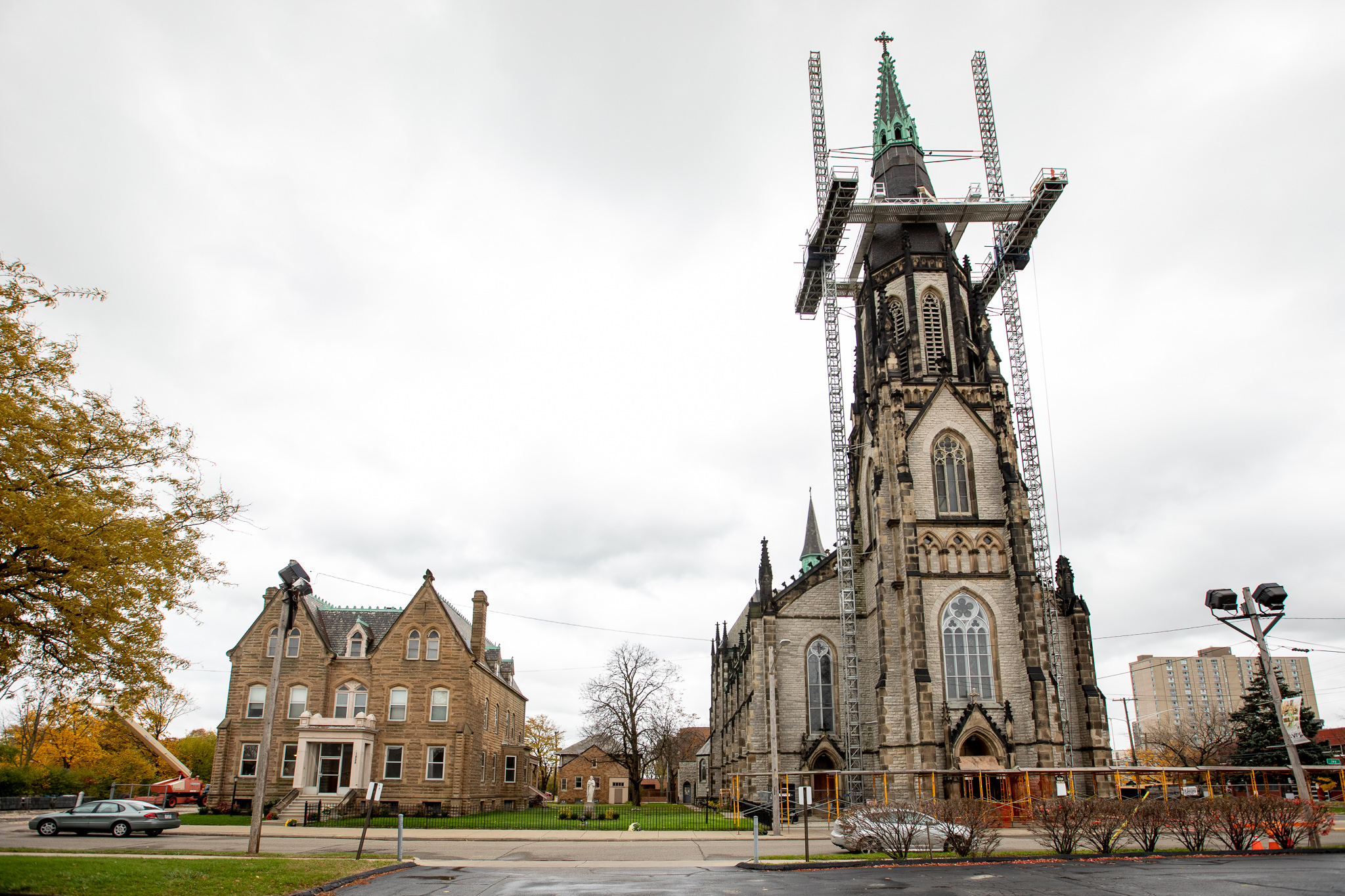 View from across the street of a three-story duplex and tall Gothic church. The church has a green copper steeple with scaffolding around it.