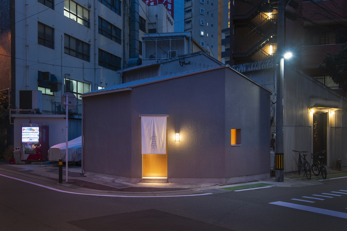 A small building on a street corner glows through a single door on one facade and a tiny window on the other.