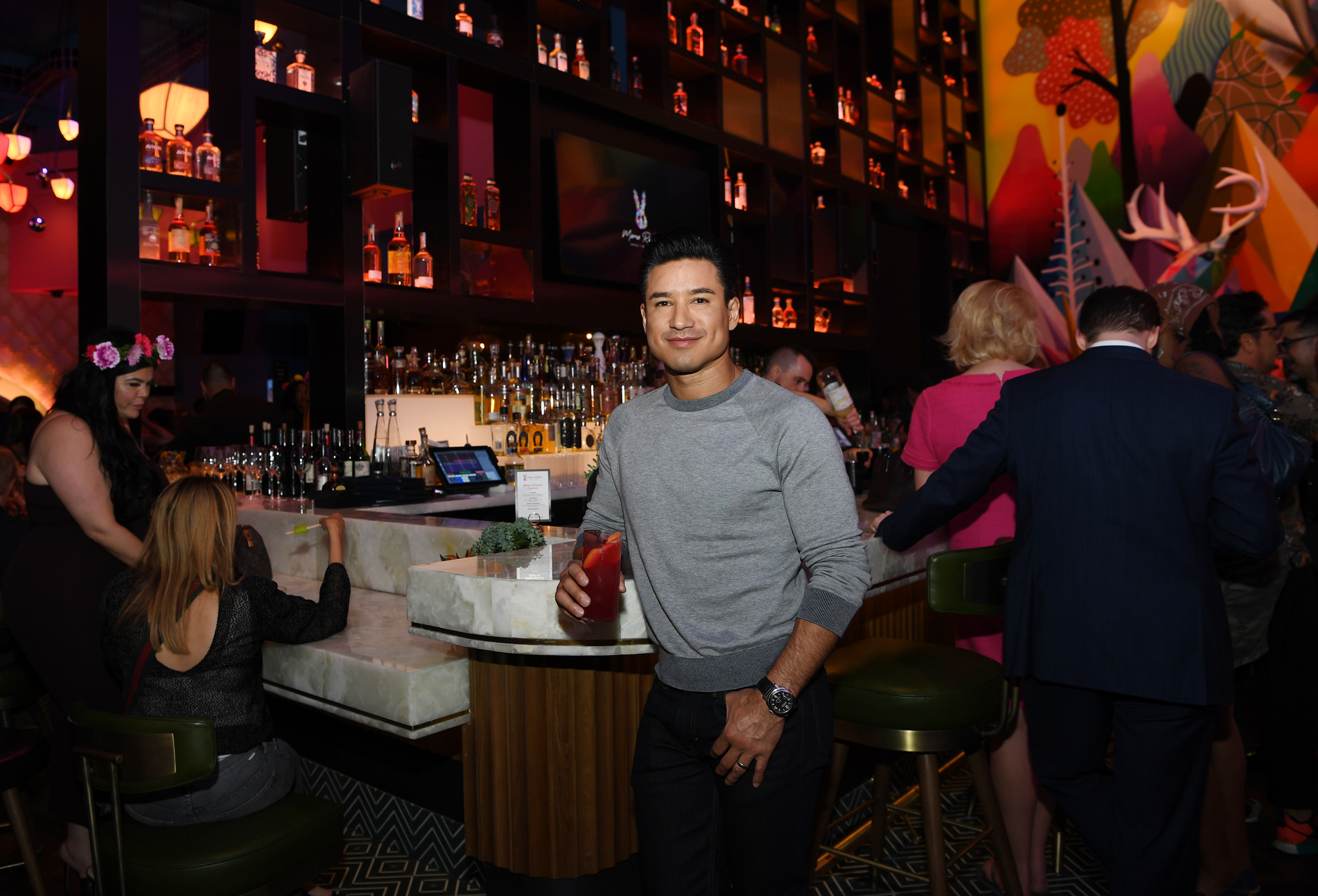 A man stands in front of a bar with a cocktail