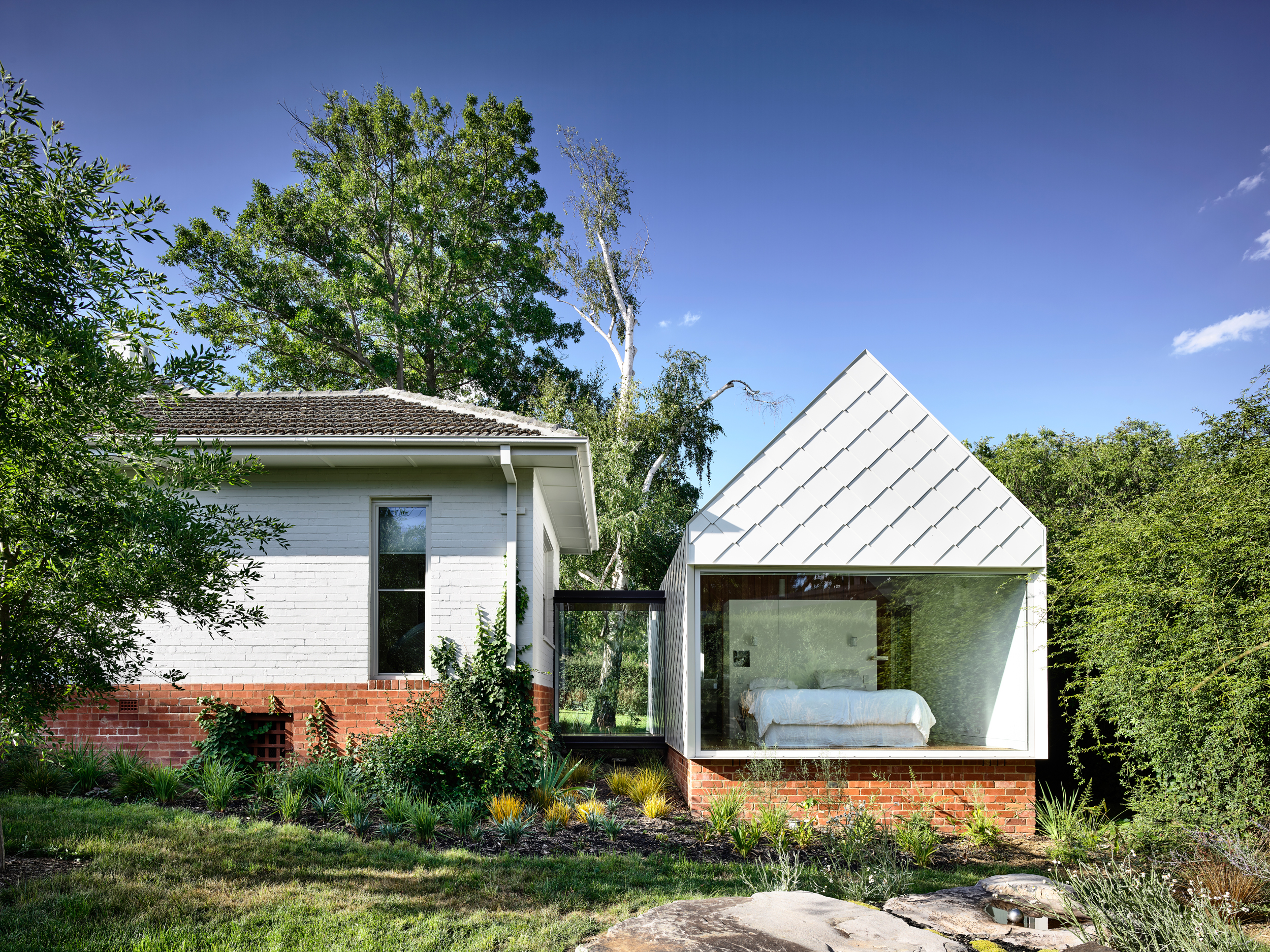 A glass-enclosed walkway connects a low-slung traditional cottage with a new pitch-roofed addition with a glass wall, which reveals a bedroom inside.