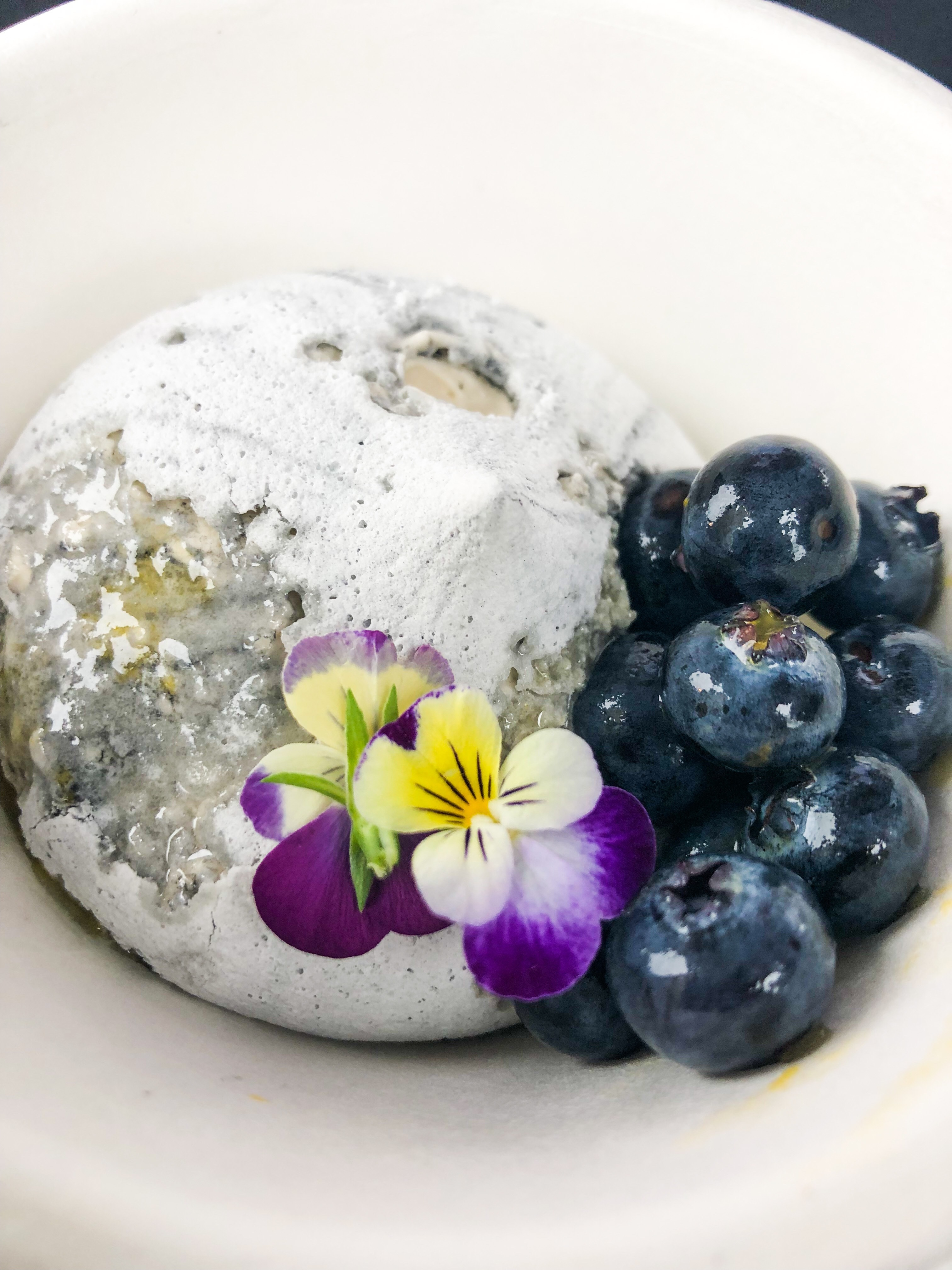 A picture of a meringue-looking pavlova with an edible flower and fresh blueberries