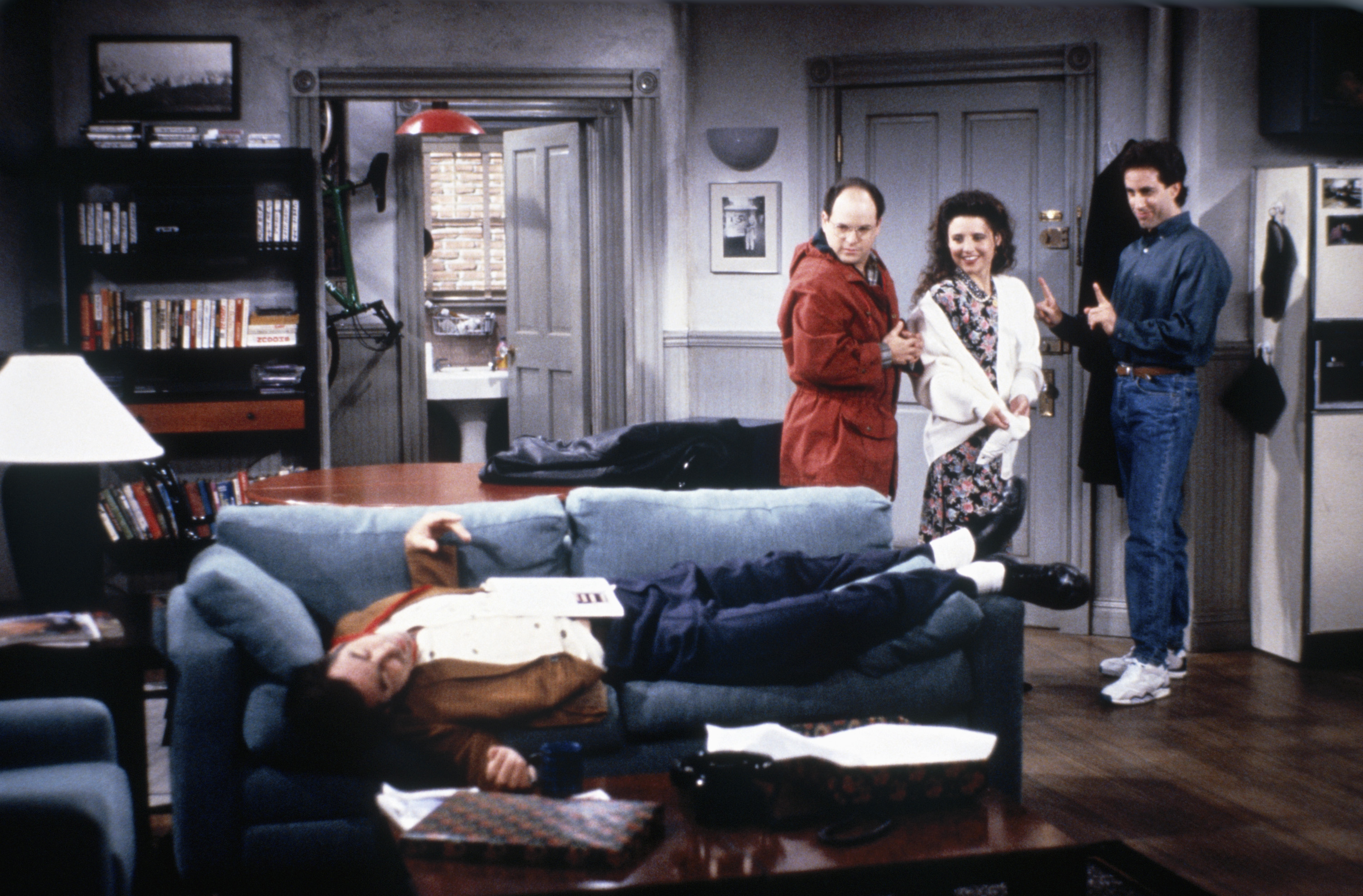 """Seinfeld"" characters George, Elaine, and Jerry stand in Jerry's apartment and look at Kramer passed out on the couch."
