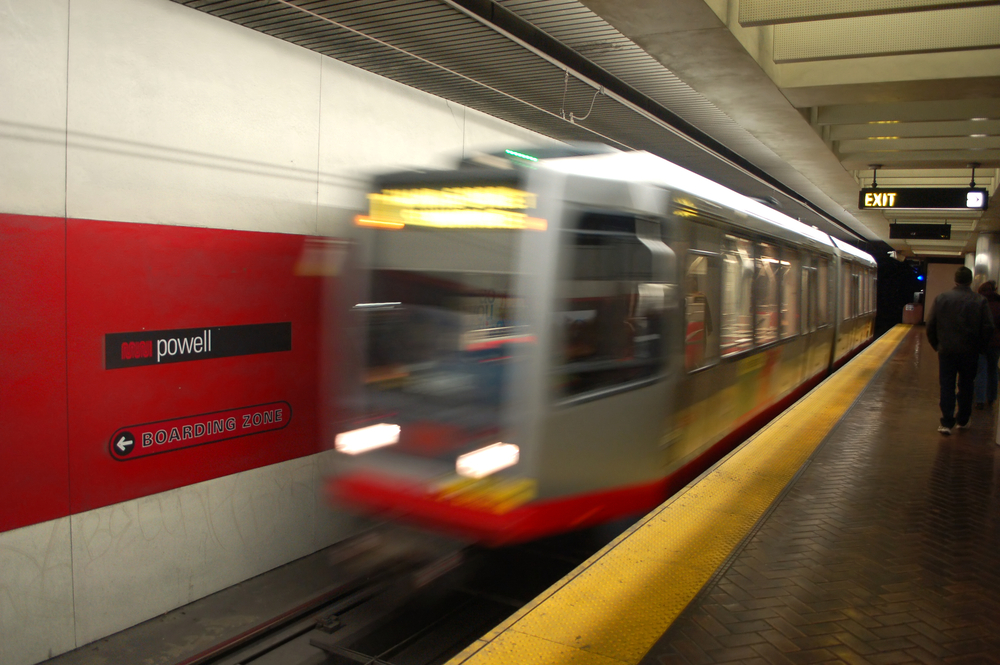 The front of a Muni light-rail train, blurred as it accelerates into a station stop.