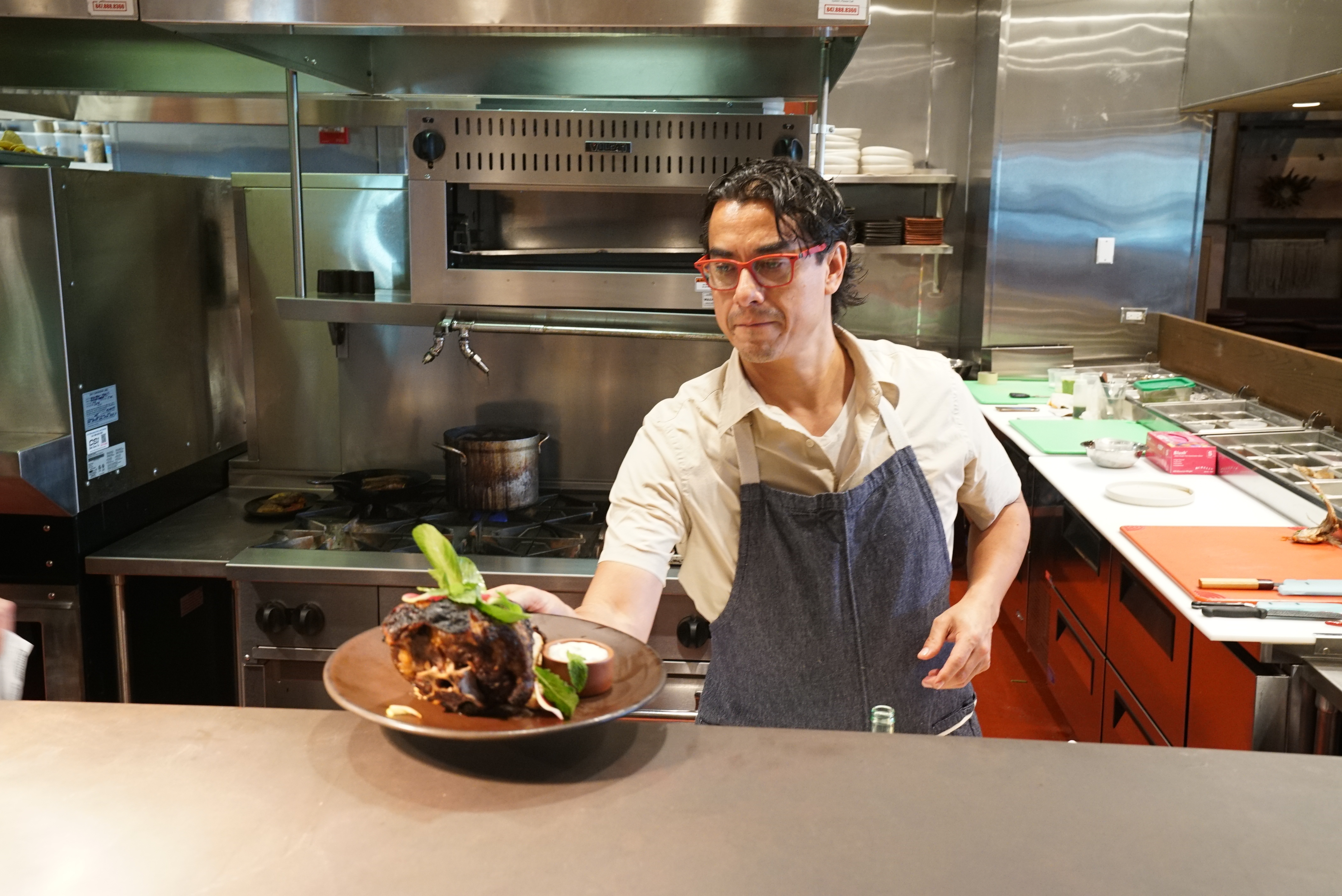 Carlos Gaytan putting out a dish from behind the kitchen counter.
