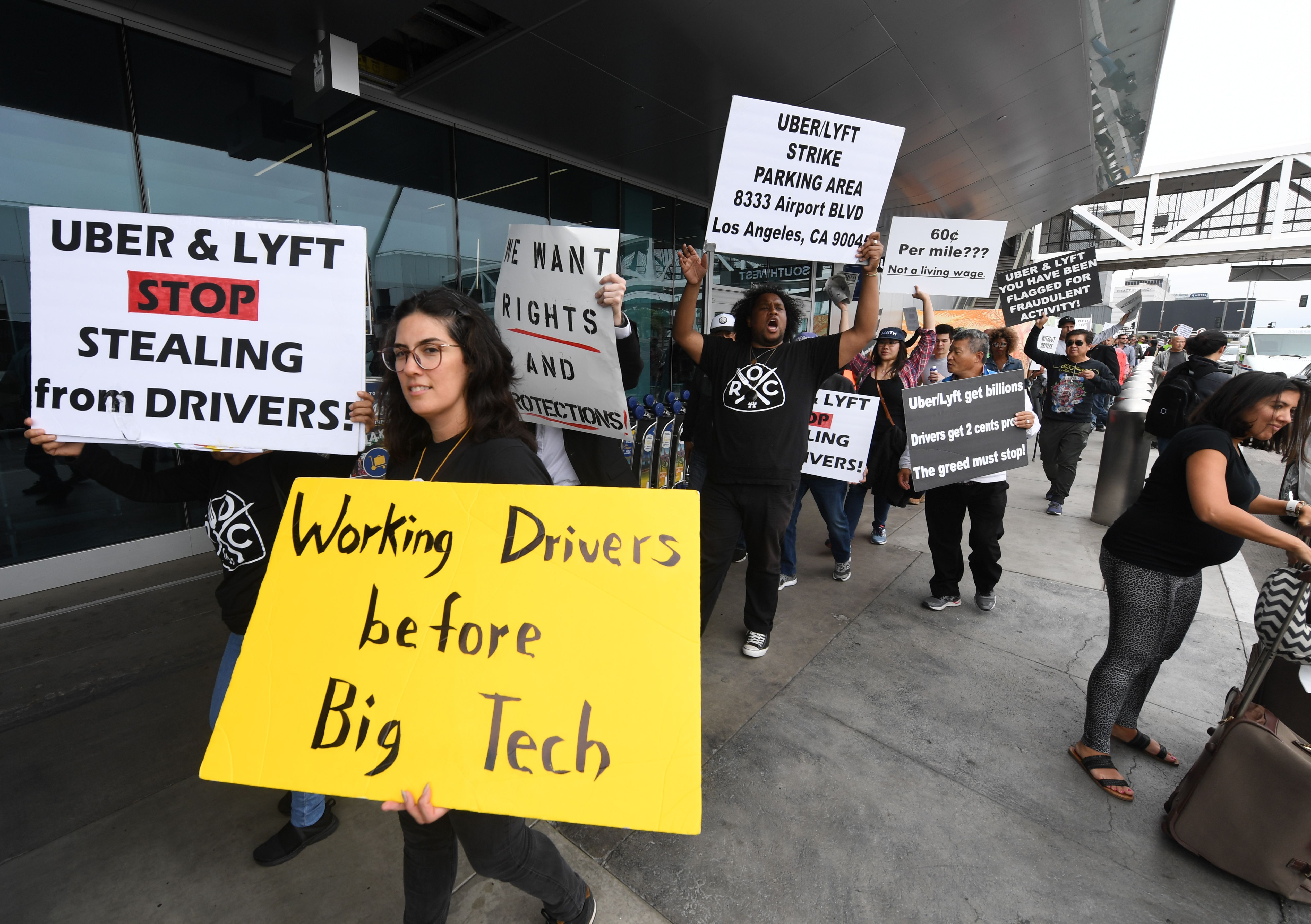 "A group of people protesting Uber and Lyft over how it pays and treats its drivers. One woman is in the forefront holding a sign that reads ""Working Drivers before Big Tech."""