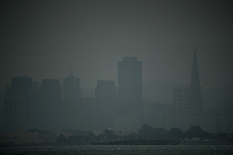 Tall buildings barely visible as silhouettes through a gray haze of smoke.