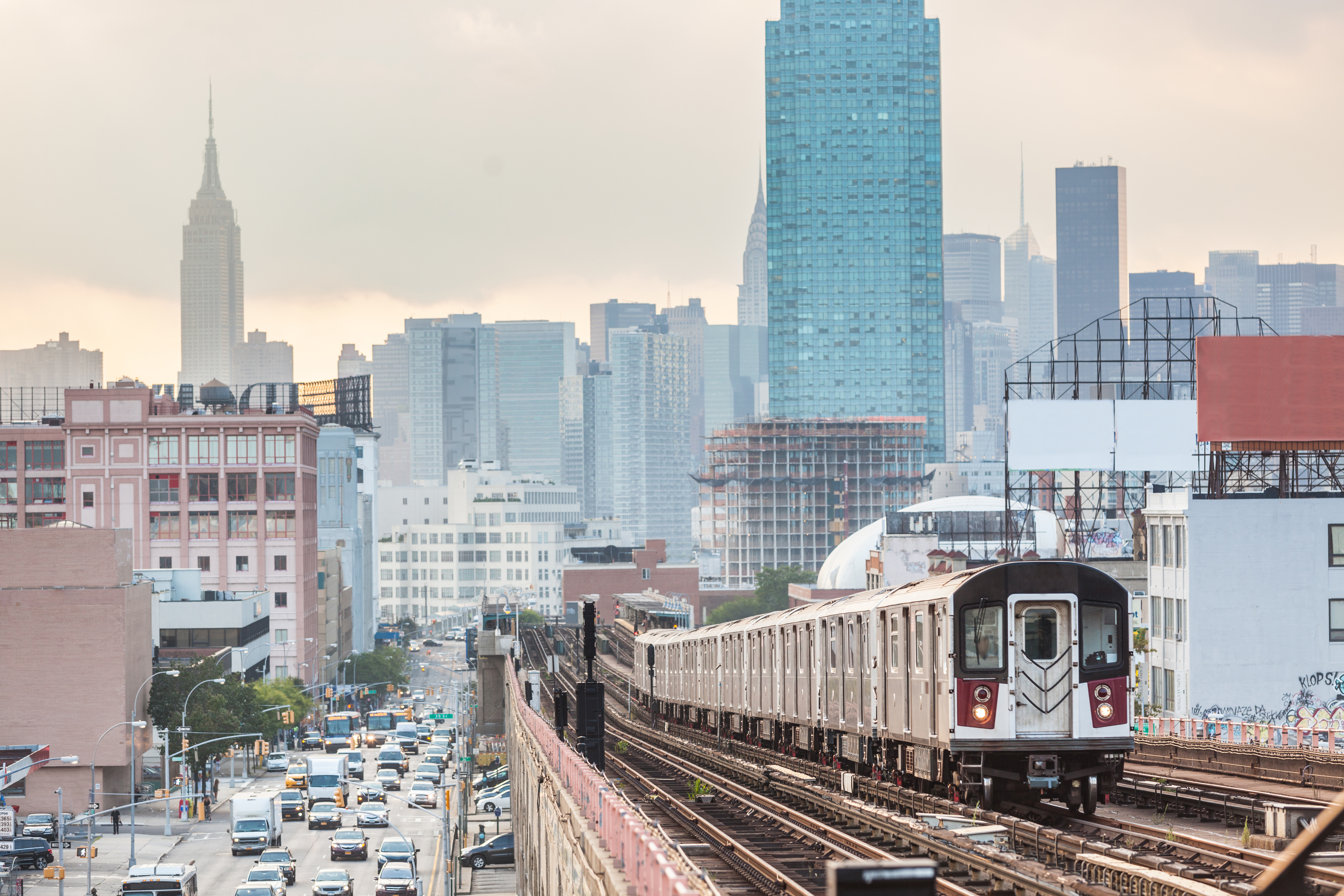 A subway travels above ground in NYC, the Manhattan skyline can be seen at the back.