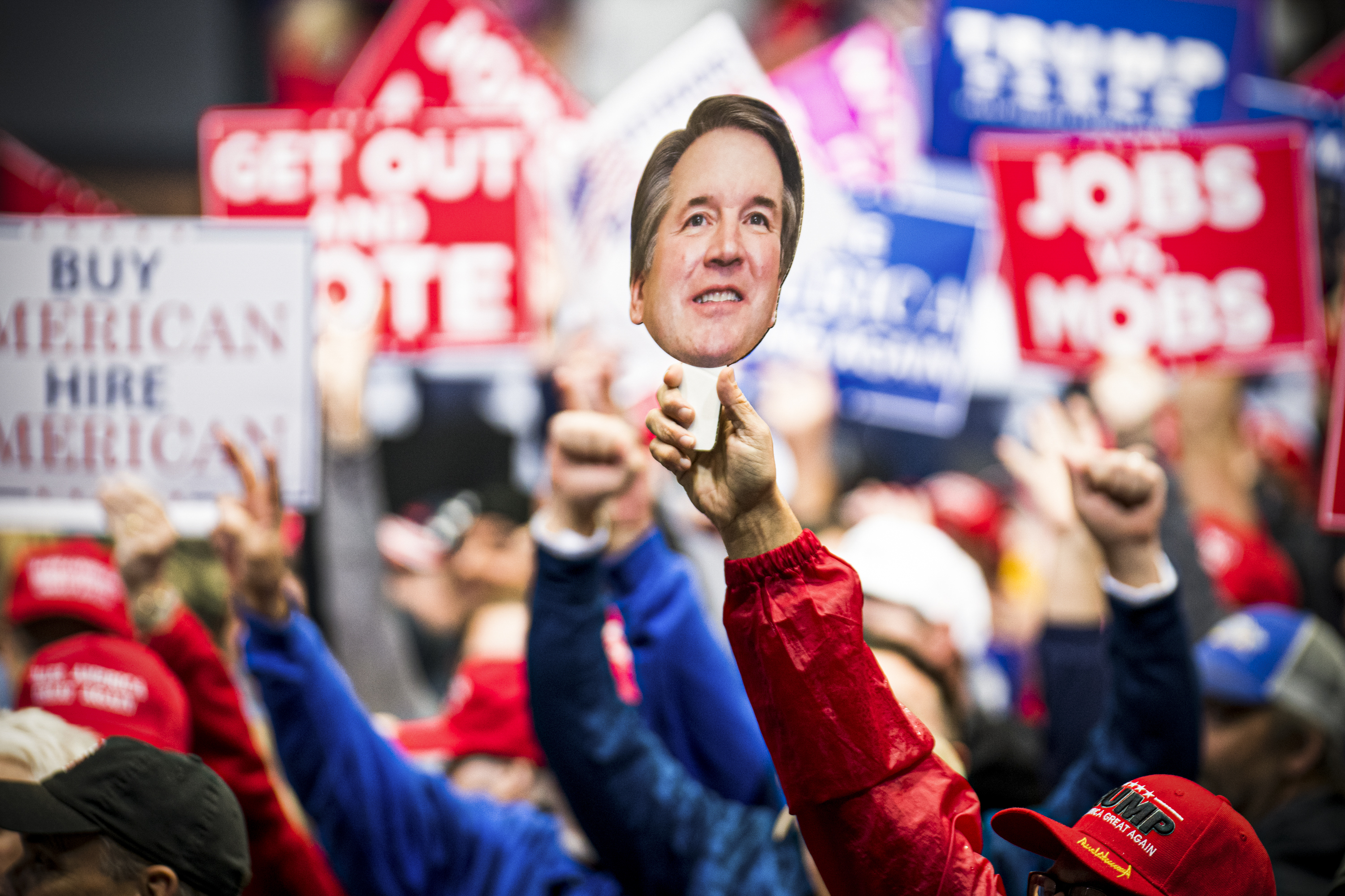 Hands in a rally crowd hold up a picture of Supreme Court Justice Brett Kavanaugh.