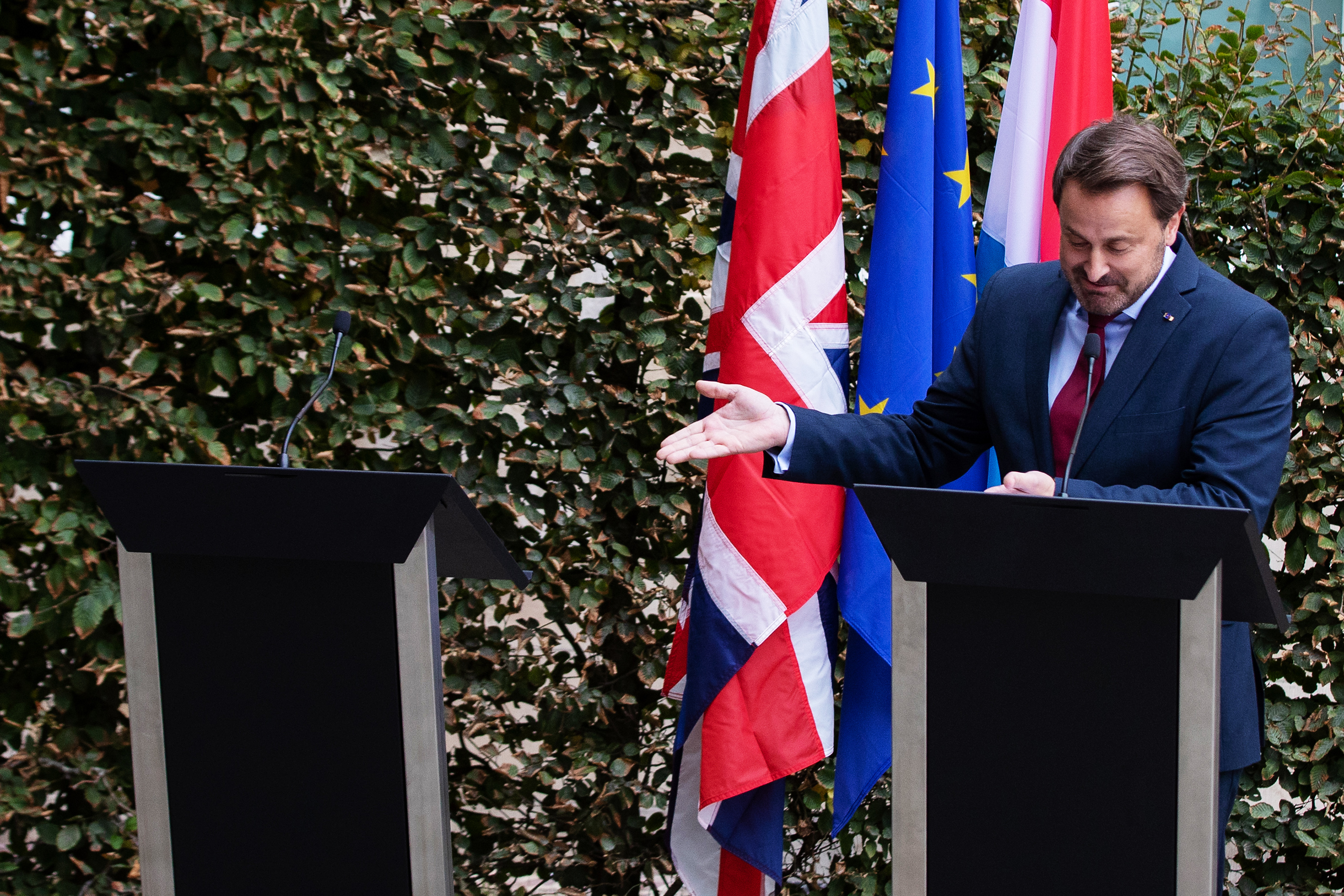 Luxembourg Prime Minister Xavier Bettel stands at a podium and gestures to another podium, which has no one standing behind it.