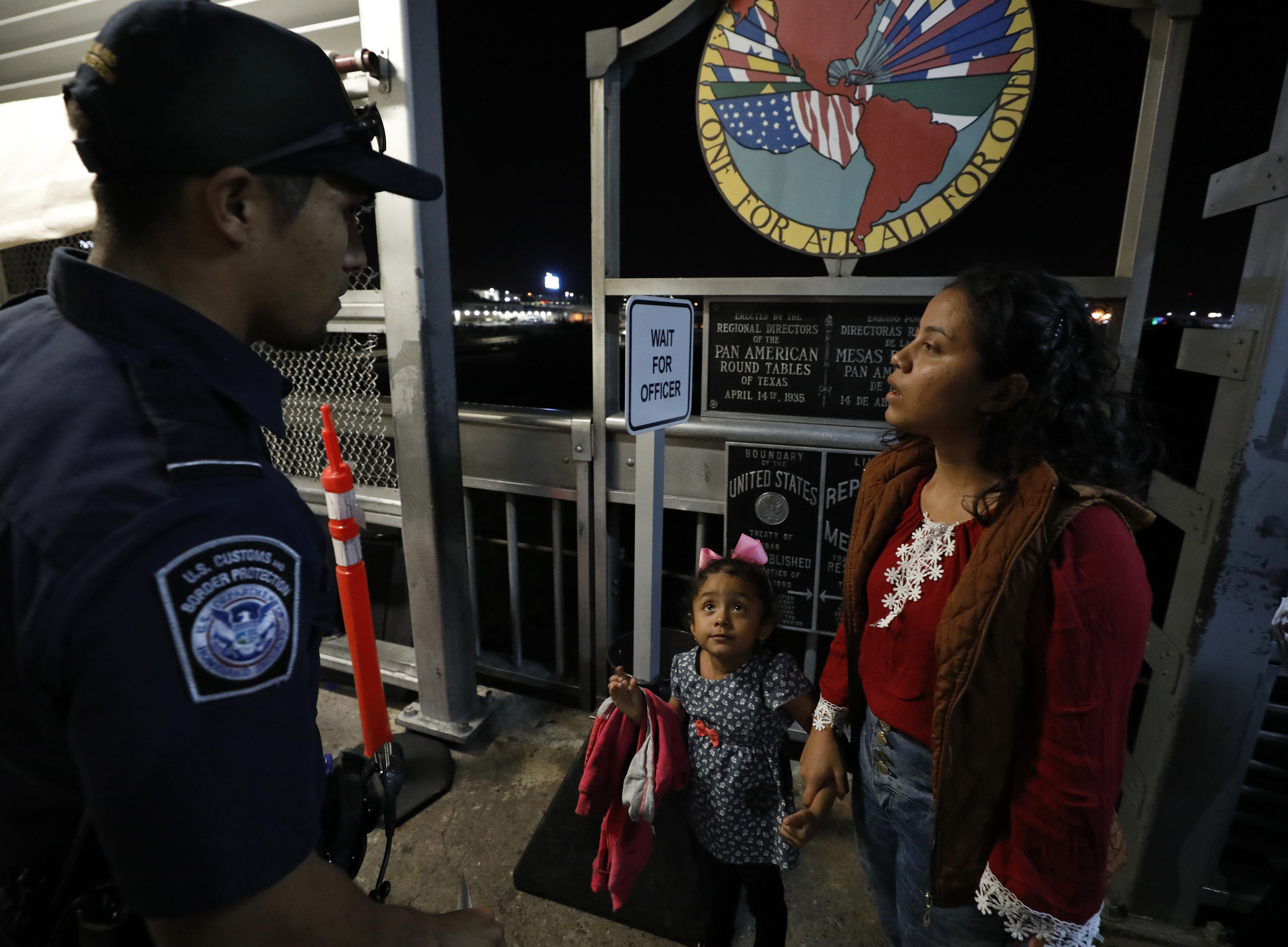 A U.S. Customs and Border Protection officer, left, talks with Honduran migrants Natalie Amador, 4, and her mother Alejandra Amador, 24, as they wait to cross International Bridge No. 1 for their first hearing at the tent court facility, Monday, Sept. 16, 2019, in Laredo, Texas. The migrants were sent back to Mexico under the Migrant Protection Protocols.