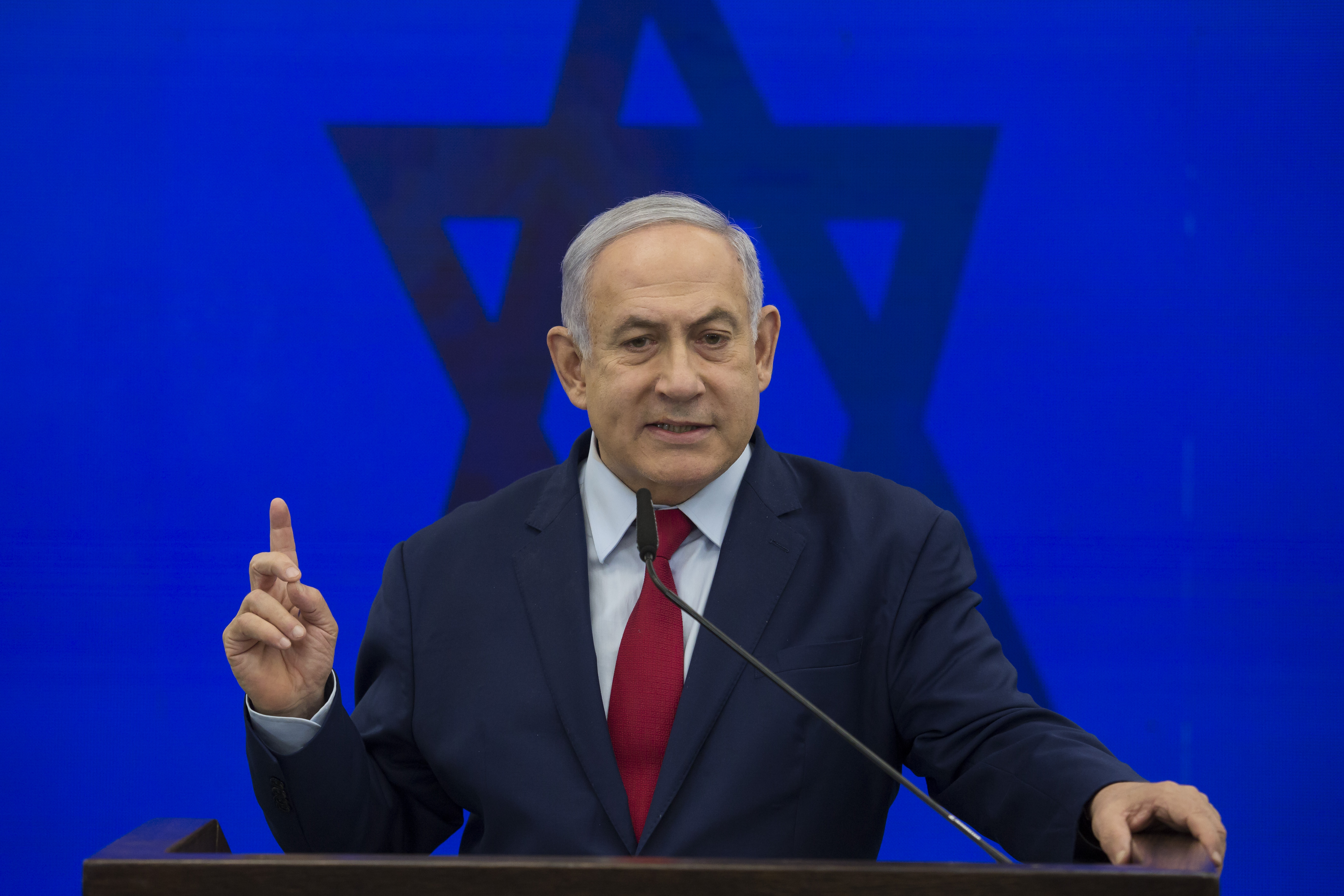 Israeli Prime Minister Benjamin Netanyahu standing at a podium backed by a Jewish star and holding up a finger.