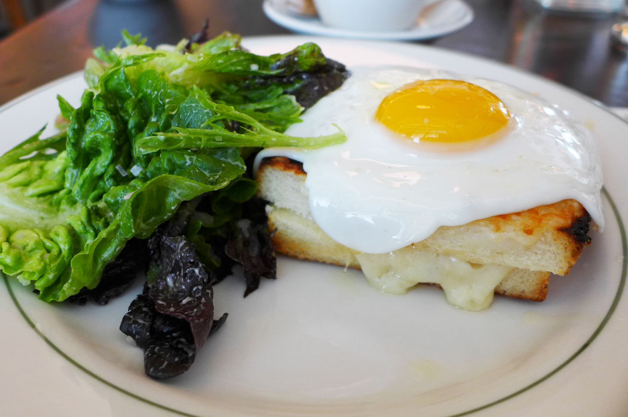A toasted cheese sandwich with a fried egg on top, next to a simple salad...