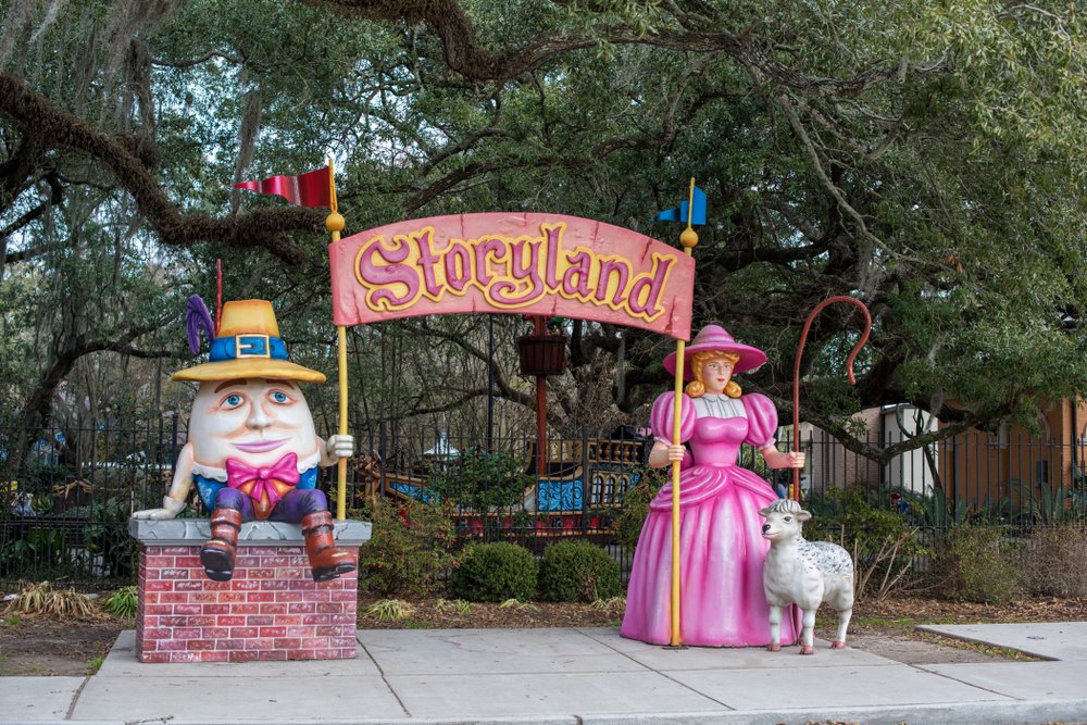 Two large fiberglass story tale characters stand in front of a tree-lined park