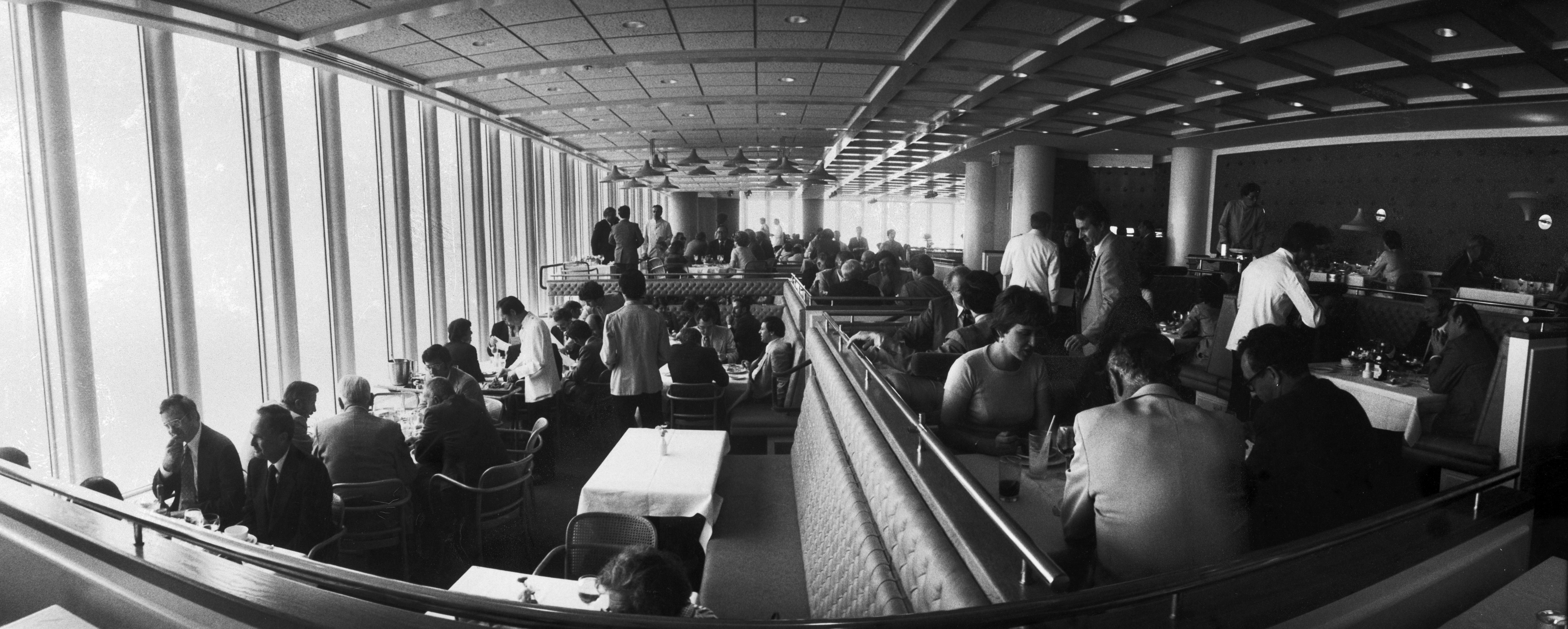 A panoramic view of the Windows on the World dining room, from the floor-to-ceiling windows on the left to the bar on the right.