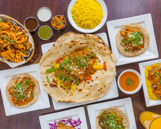 A spread of Indian tacos and other fusion food on squared plates.