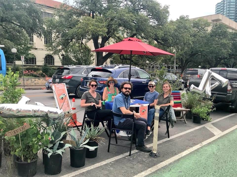 A marked street parking space filled with a patio-style table with a red umbrella, chairs, and large, potted plants. There are people seated in the chairs, facing the camera. There's a limestone Italianate building across the street behind them, indicatin