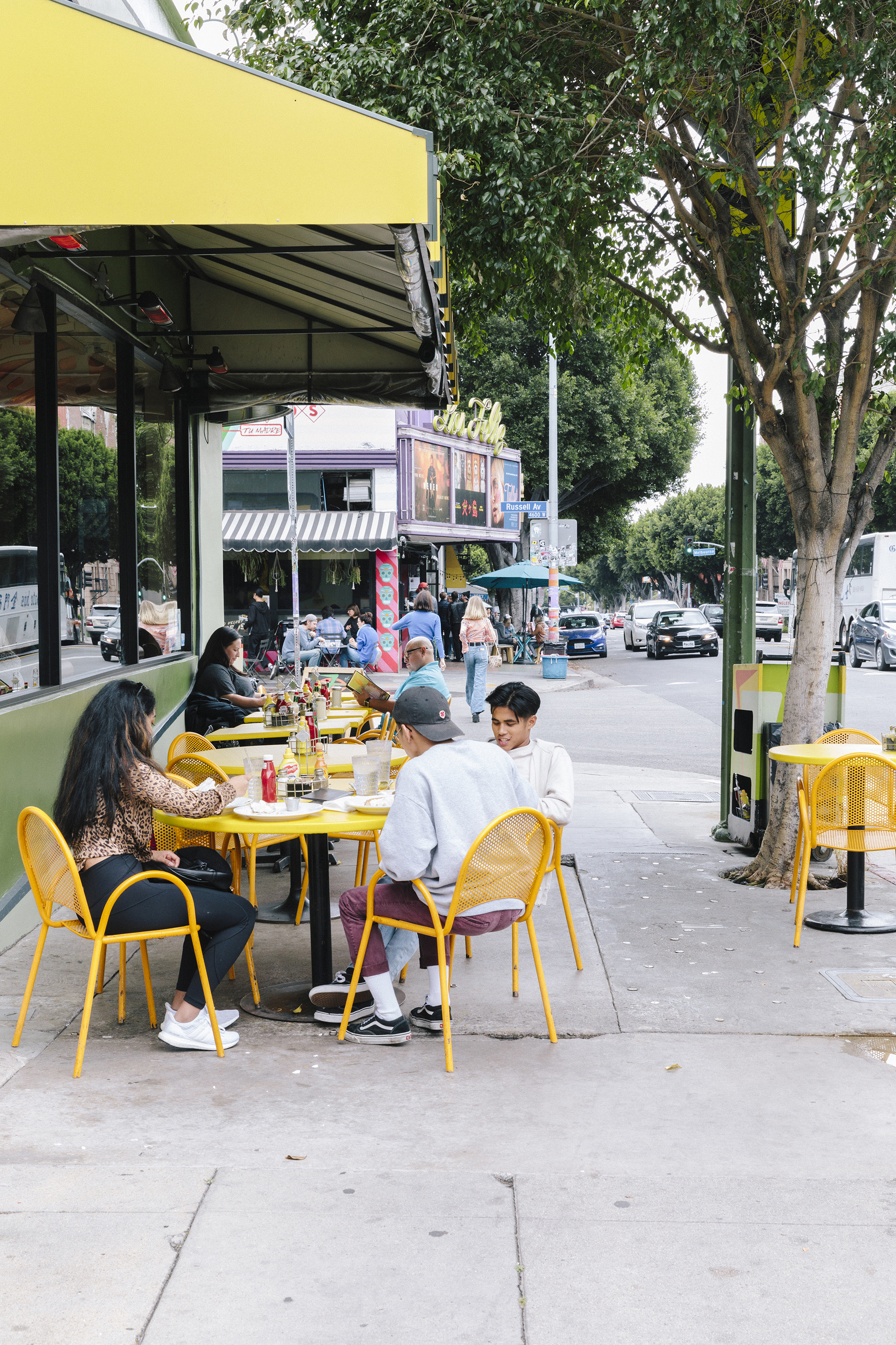 Young people sitting in yellow metal chairs dine on a sidewalk lined with trees. In the background, a vintage theater with green neon sign that reads in cursive print Los Feliz.