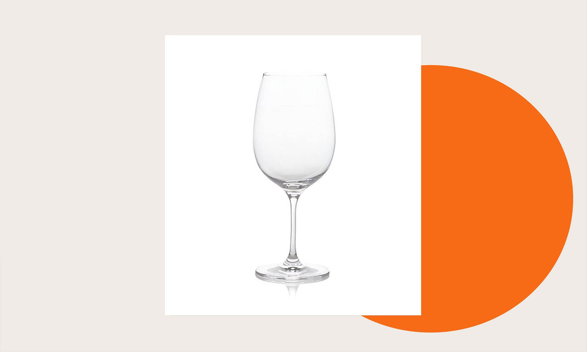 A wine glass on a cream and orange background