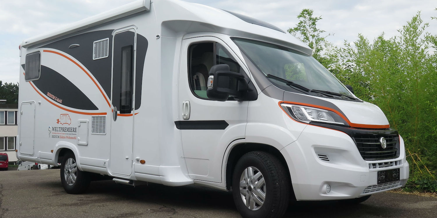 A white motorhome with black windows, black swoops on the side, and orange accent colors.