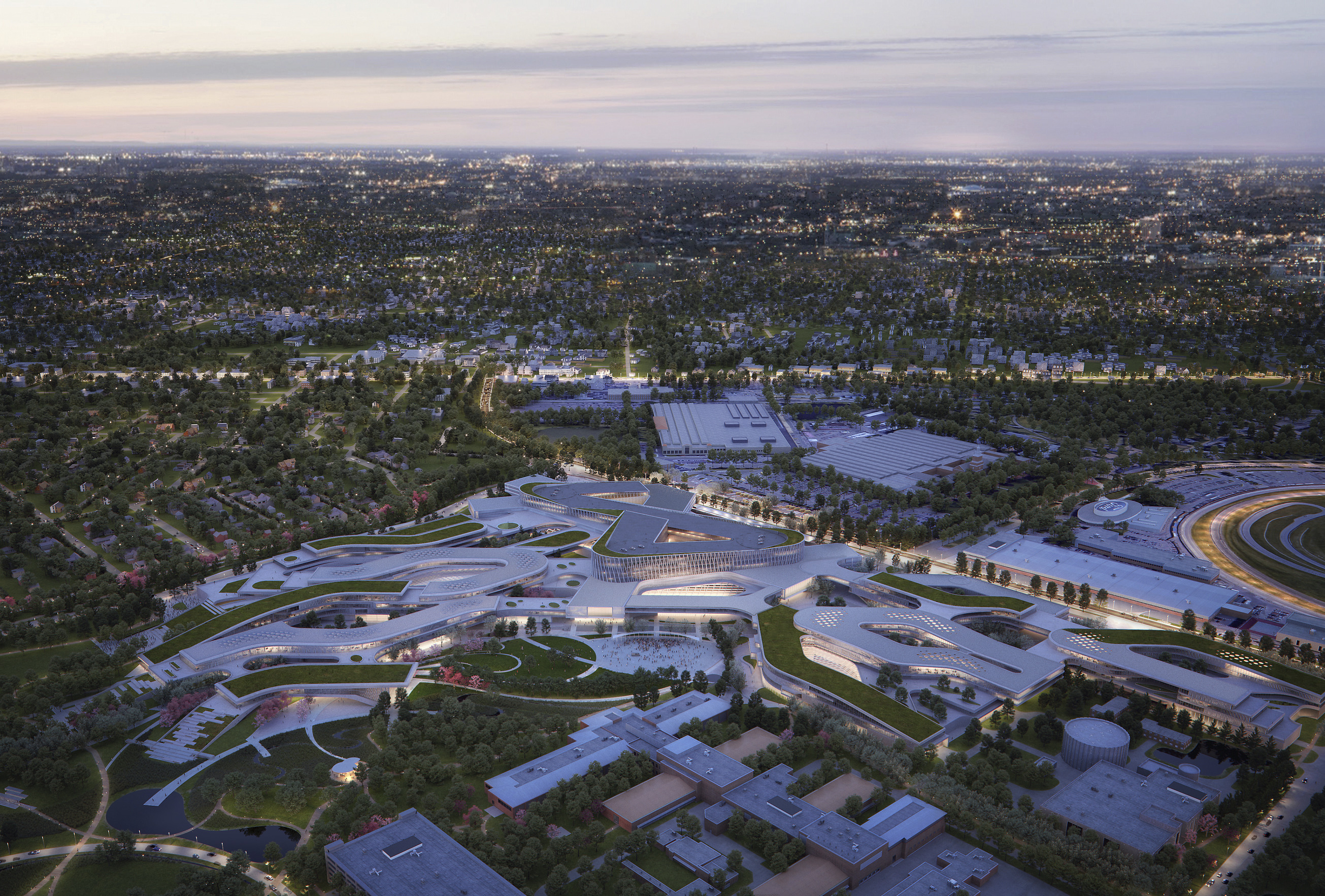 Birds-eye view of a sprawling campus of winding, low white buildings surrounded by trees. It's near sunset and the buildings have lights on.