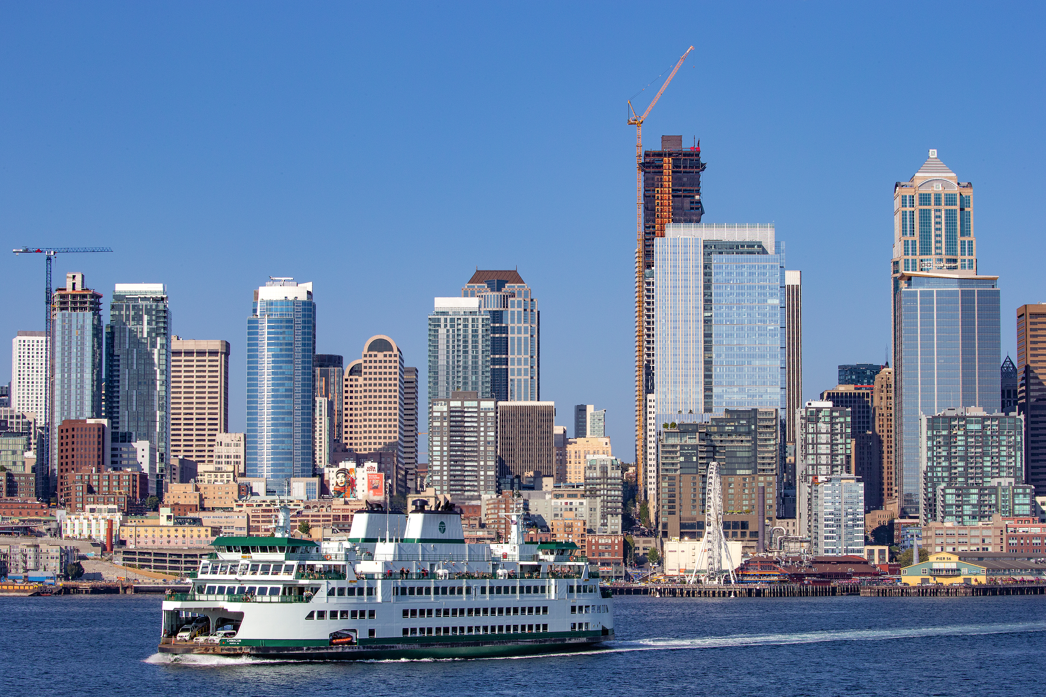 A lot of tall buildings, including ones under construction, in the background, and a passenger ferry on a harbor in the foreground.