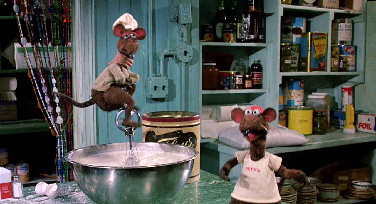 "A muppet rat sitting on an egg beater, which stands up in a metal bowl, and a second muppet rat wearing a t-shirt that says ""pete's""."