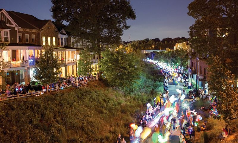 Revelers beside an urban trail watch from both side of a lantern parade.
