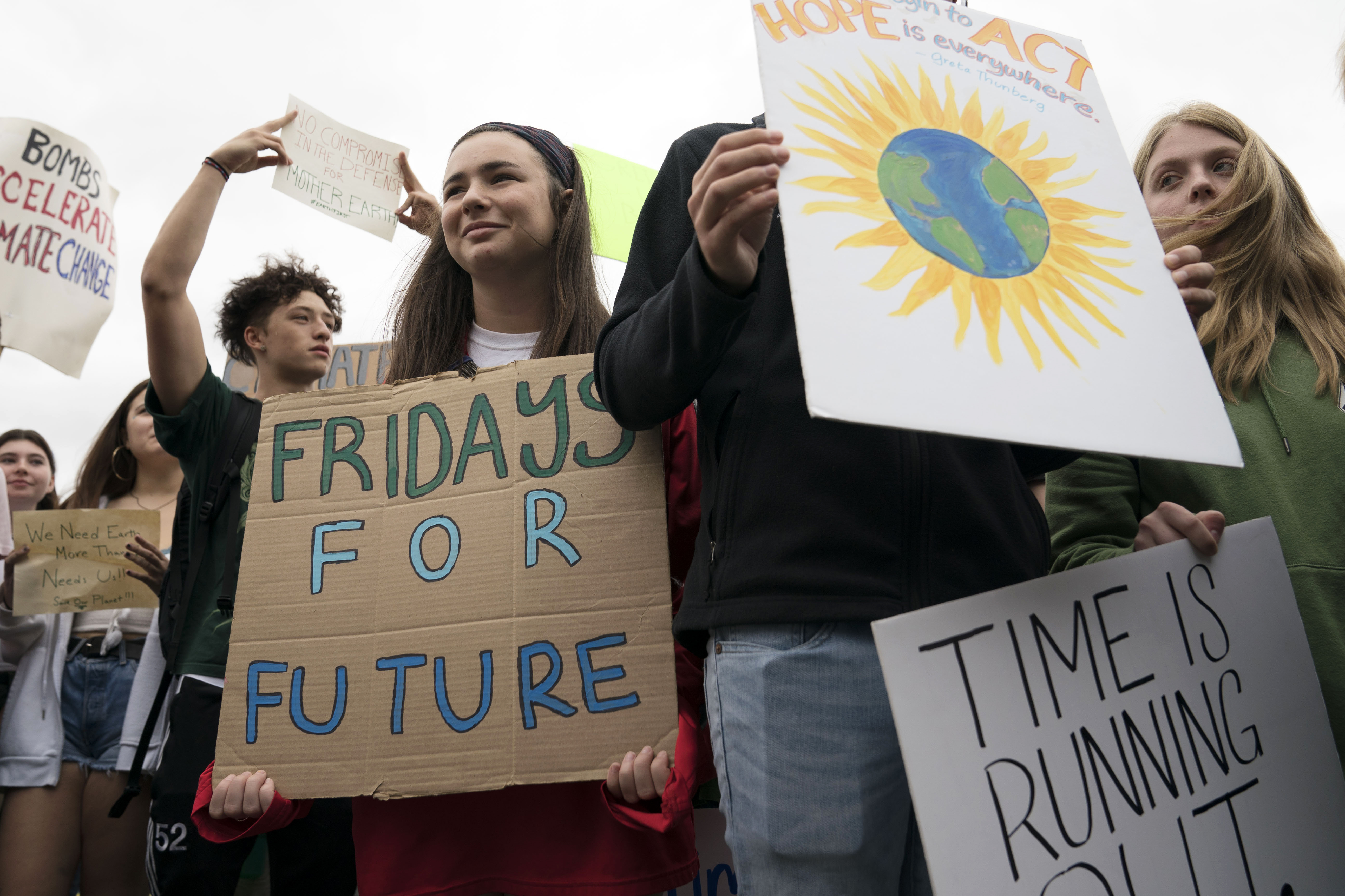 """A crowd of teenagers and a demonstration holding sings reading """"Fridays for Future"""" and """"Time is Running Out."""""""