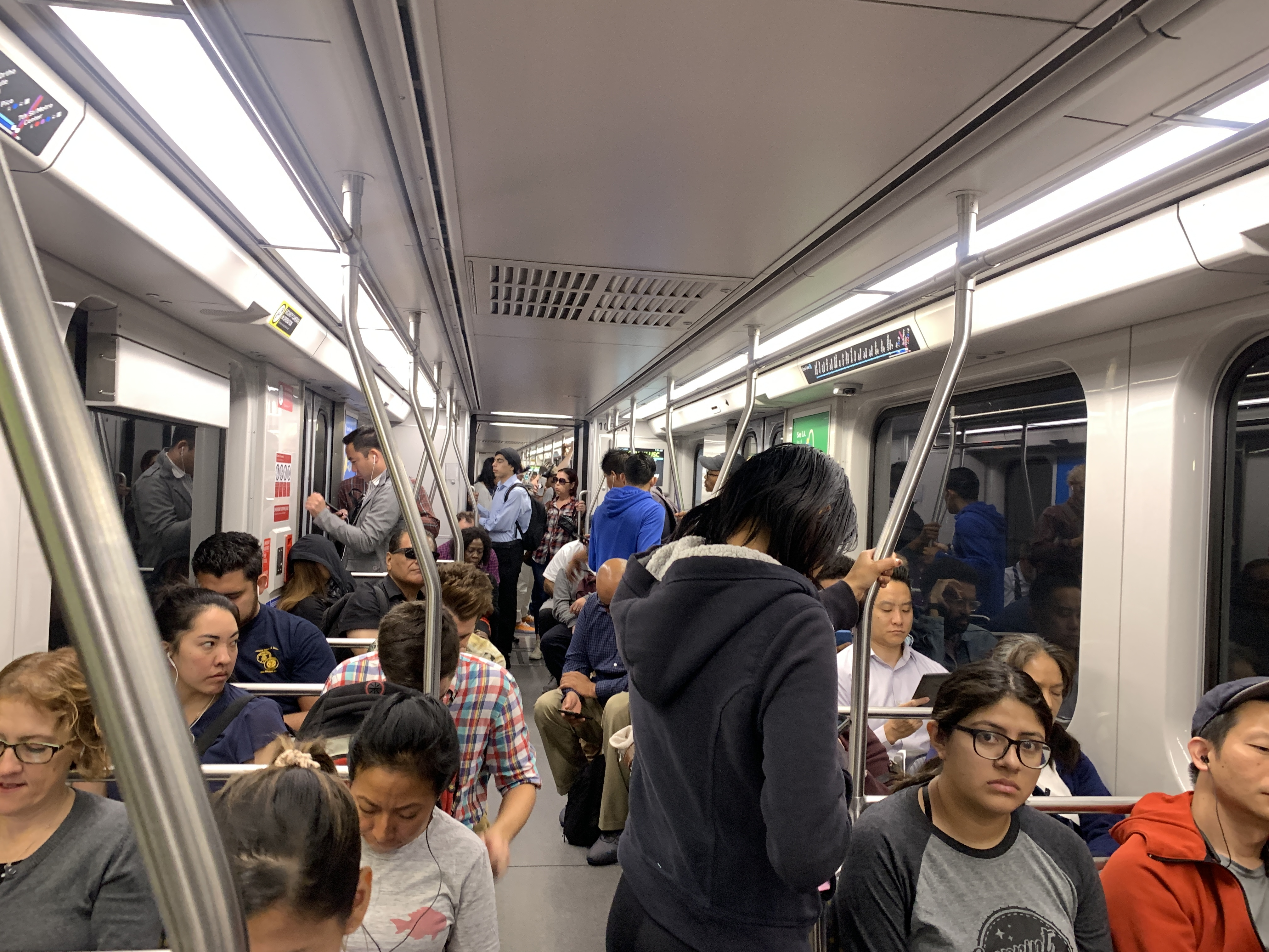 A mix of men and women of different ages and ethnicities sit and stand inside a train.