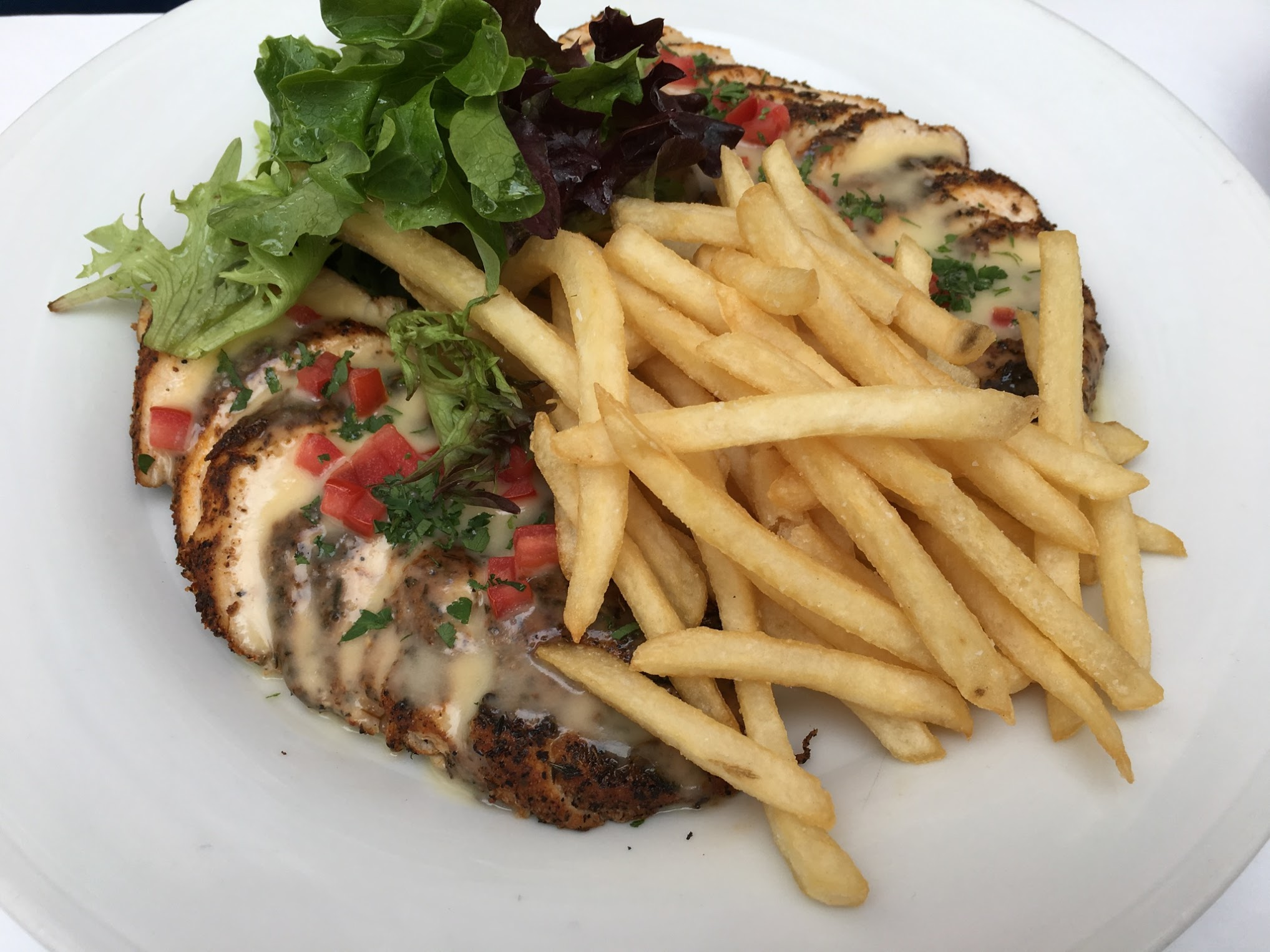 A close-up photo of the Cajun chicken dish at Le Bilboquet, which consists of sliced chicken piece underneath a bed of fries with salad behind the fries