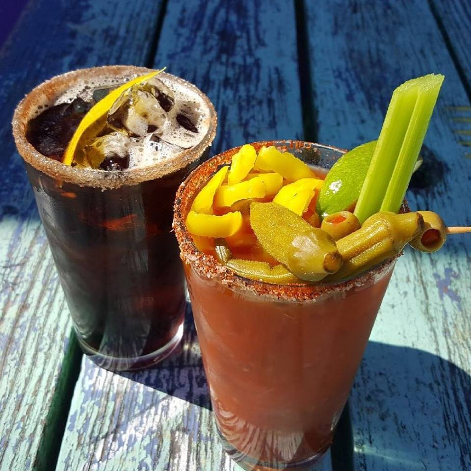 A dark brown beverage and red bloody mary topped with okra
