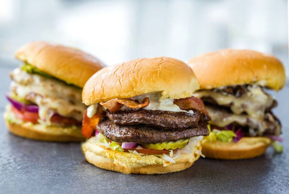 Three different double cheeseburgers on buns with a variety of toppings.