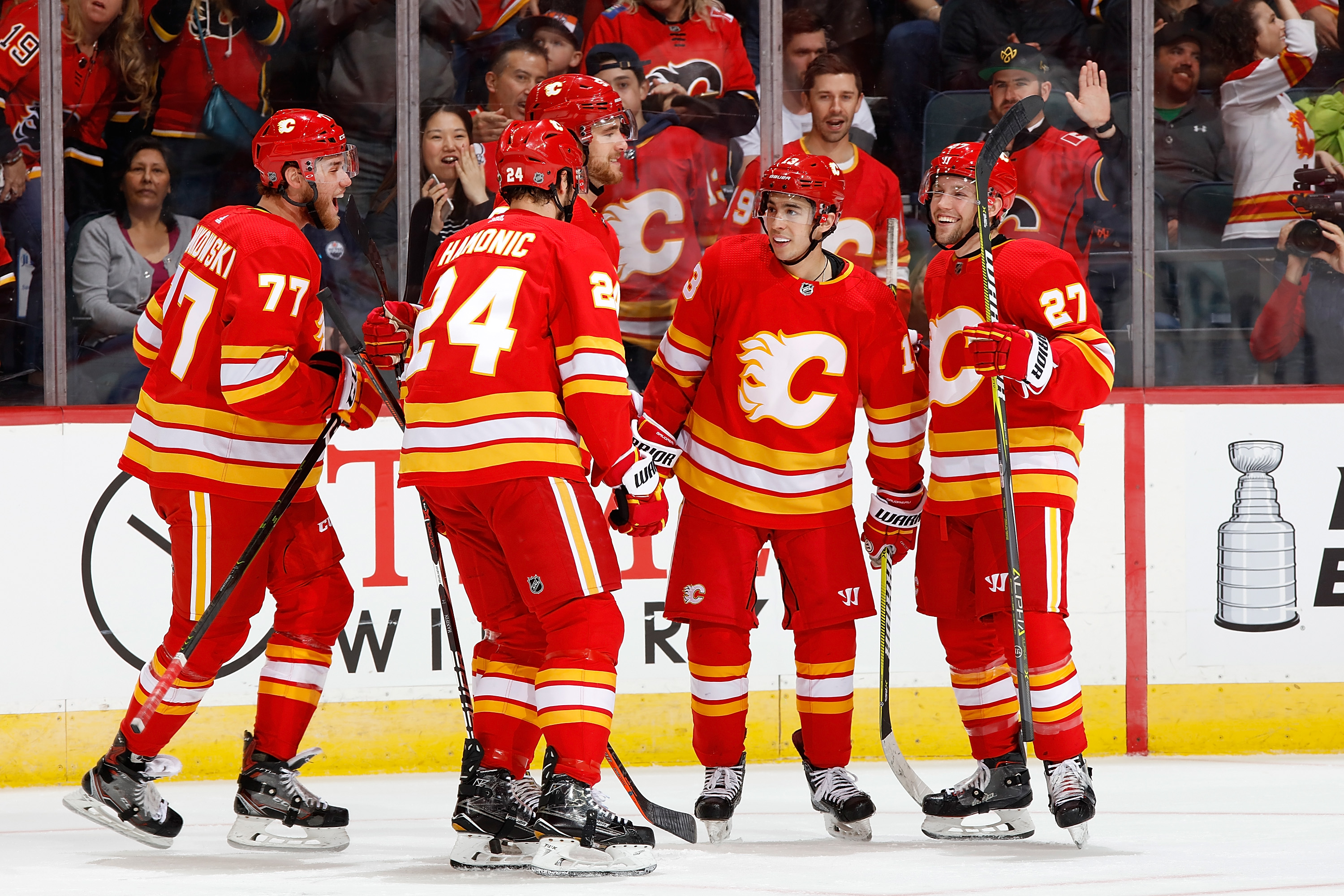 CALGARY, AB - APRIL 6: Mark Jankowski #77, Johnny Gaudreau #13 and teammates of the Calgary Flames celebrate a goal against the Edmonton Oilers during an NHL game on April 6, 2019 at the Scotiabank Saddledome in Calgary, Alberta, Canada.