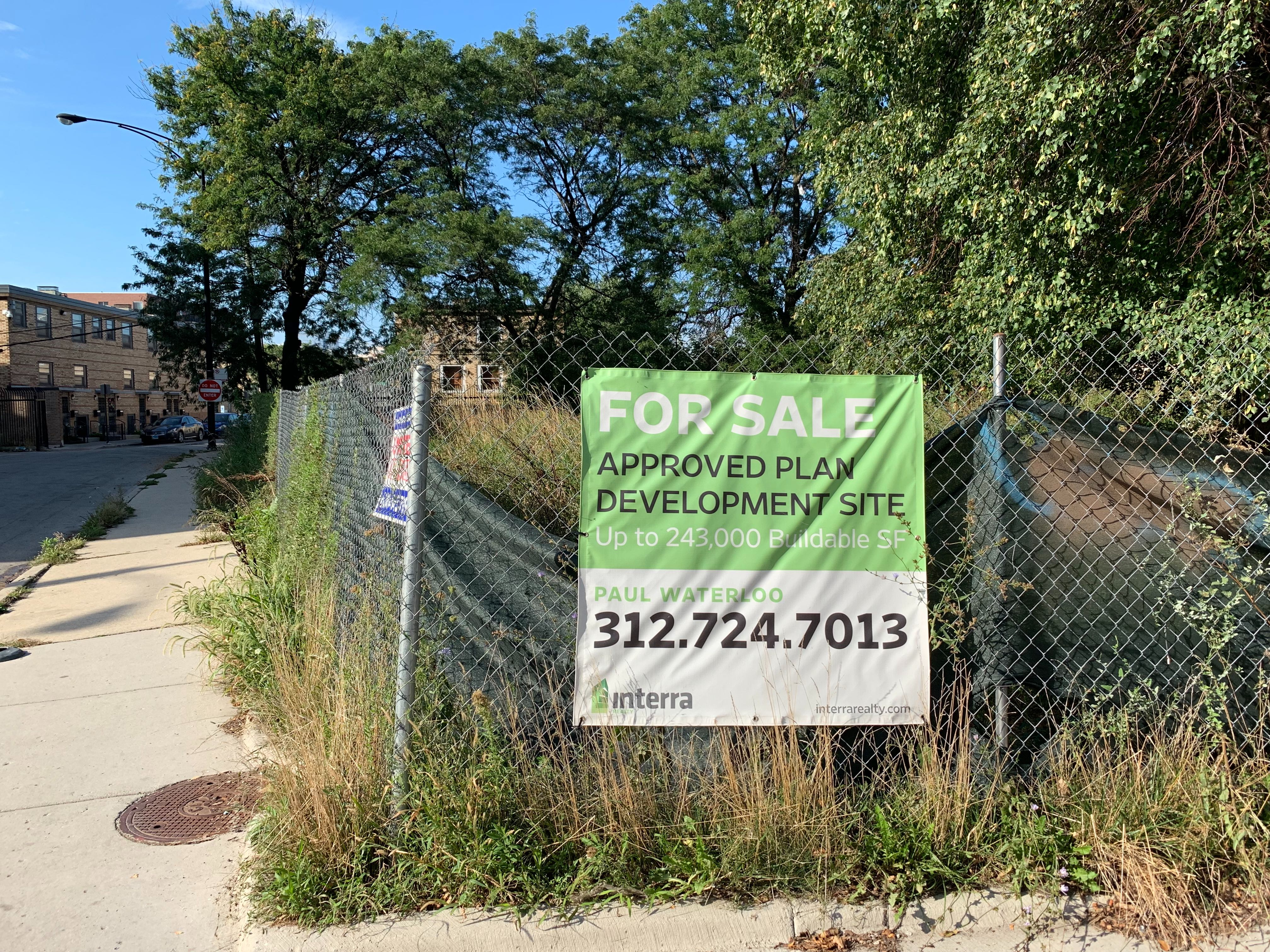 """A city lot filled with trees and bushes surrounded by a chain link fence with a """"for sale"""" sign."""