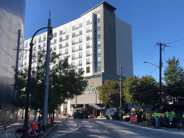 A new 11-story hotel stands over a street next to the Georgia Aquarium.