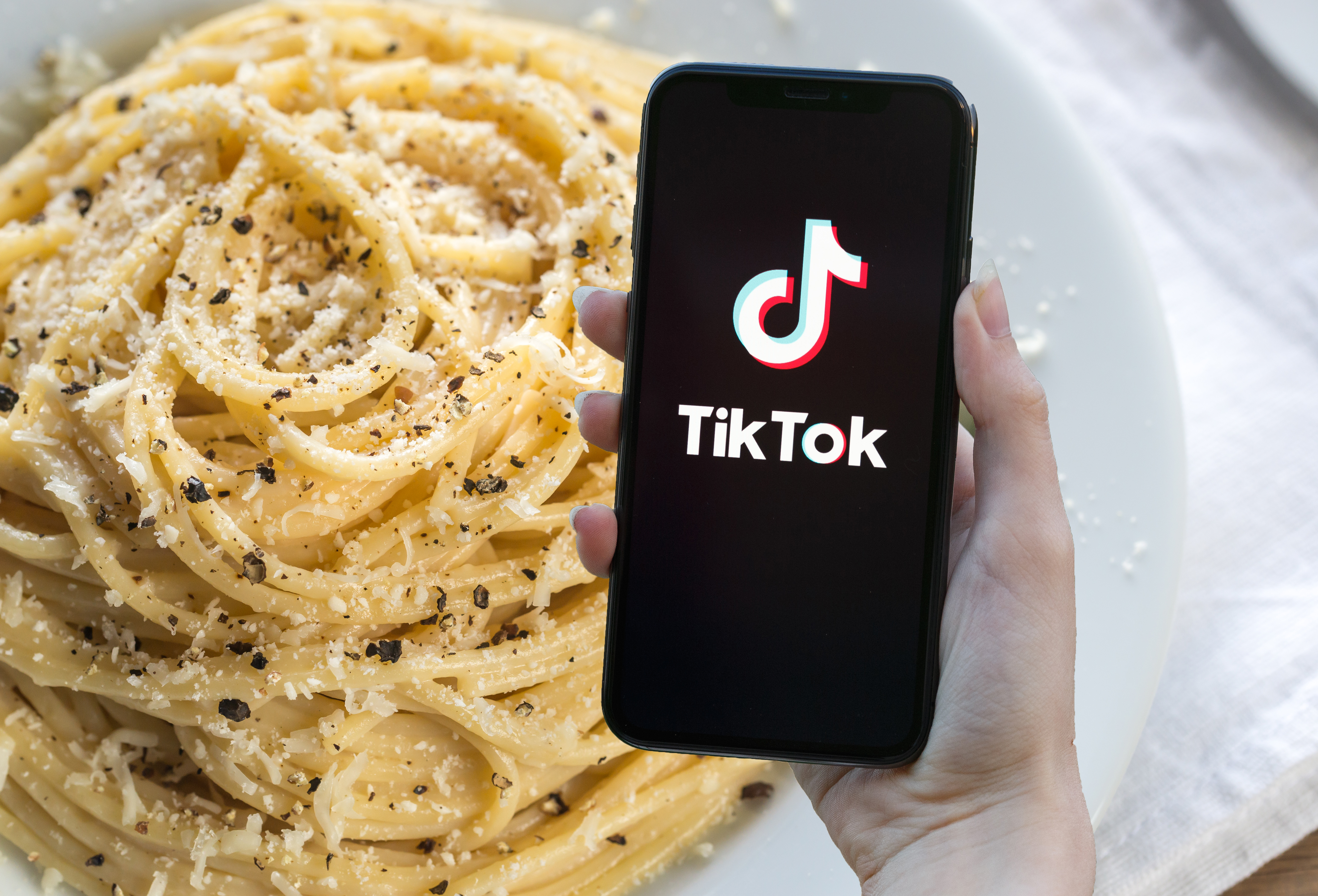 In the foregroud, a hand holds a phone displaying the Tik Tok app; the background is a plate of cacio e pepe.