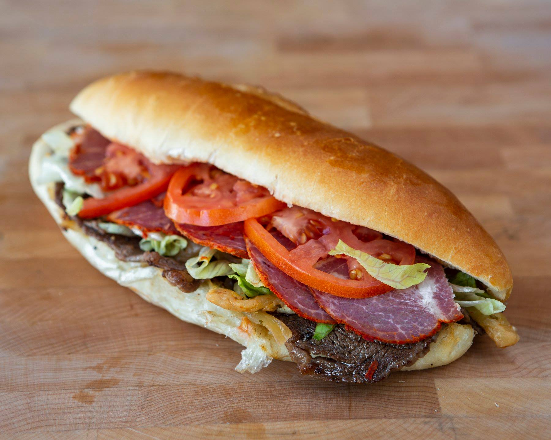 A steak-capicollo sandwich with lettuce and tomato on a long bun.