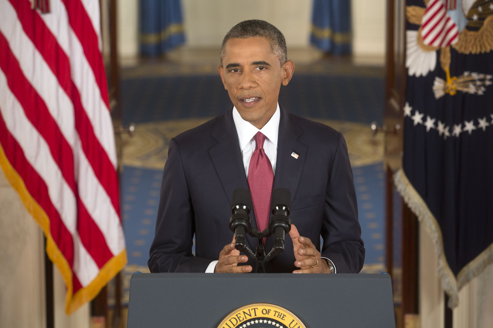 Barack Obama standing at a podium, flanked by American flags on either side.