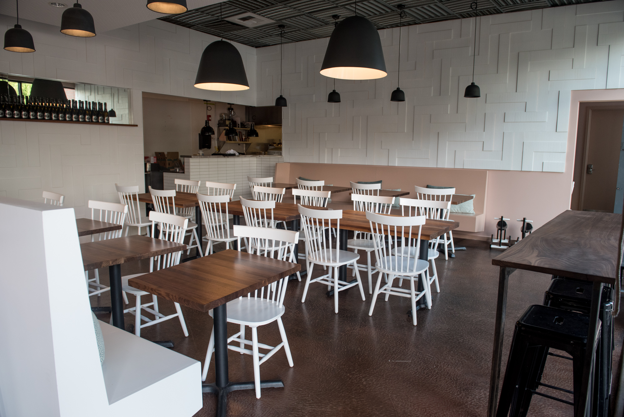 The interior of Eden Hill Provisions, with walnut wood tables, chairs, soft lighting, and a light pink accents.