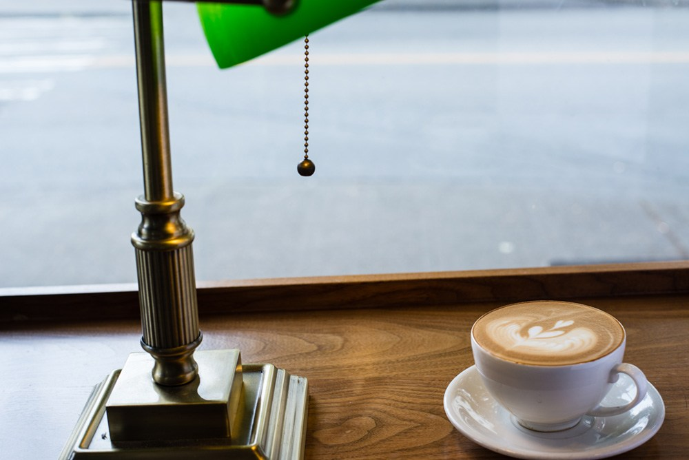 A mug of latte sits on a wooden counter next to a green desk lamp.