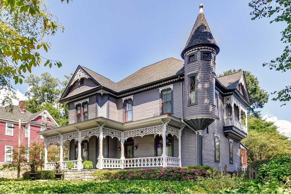 An ornate Victorian house with purplish paint and a grant turret with a nice green lawn.