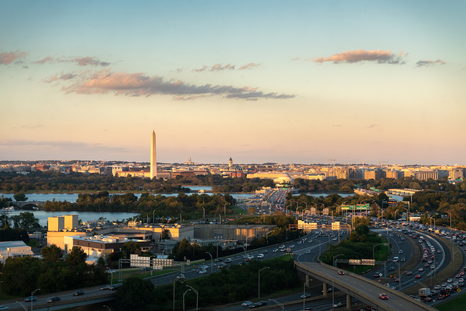 Highways, monuments, and a river are seen at sunset. A tall obelisk is in the background.
