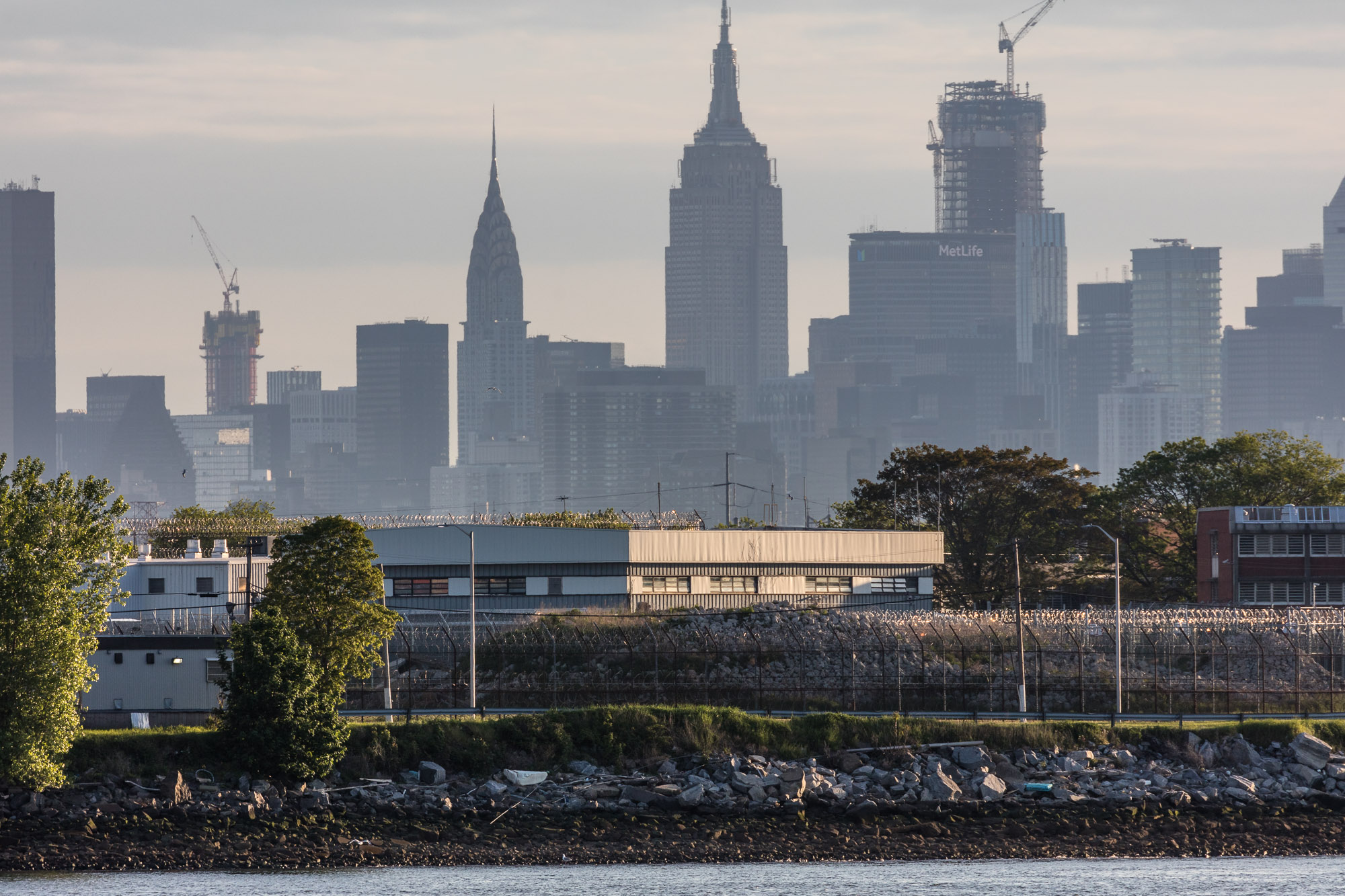 A jail on Rikers Island surrounded by barbed wire with silhouetted skyscrapers and buildings in the background.