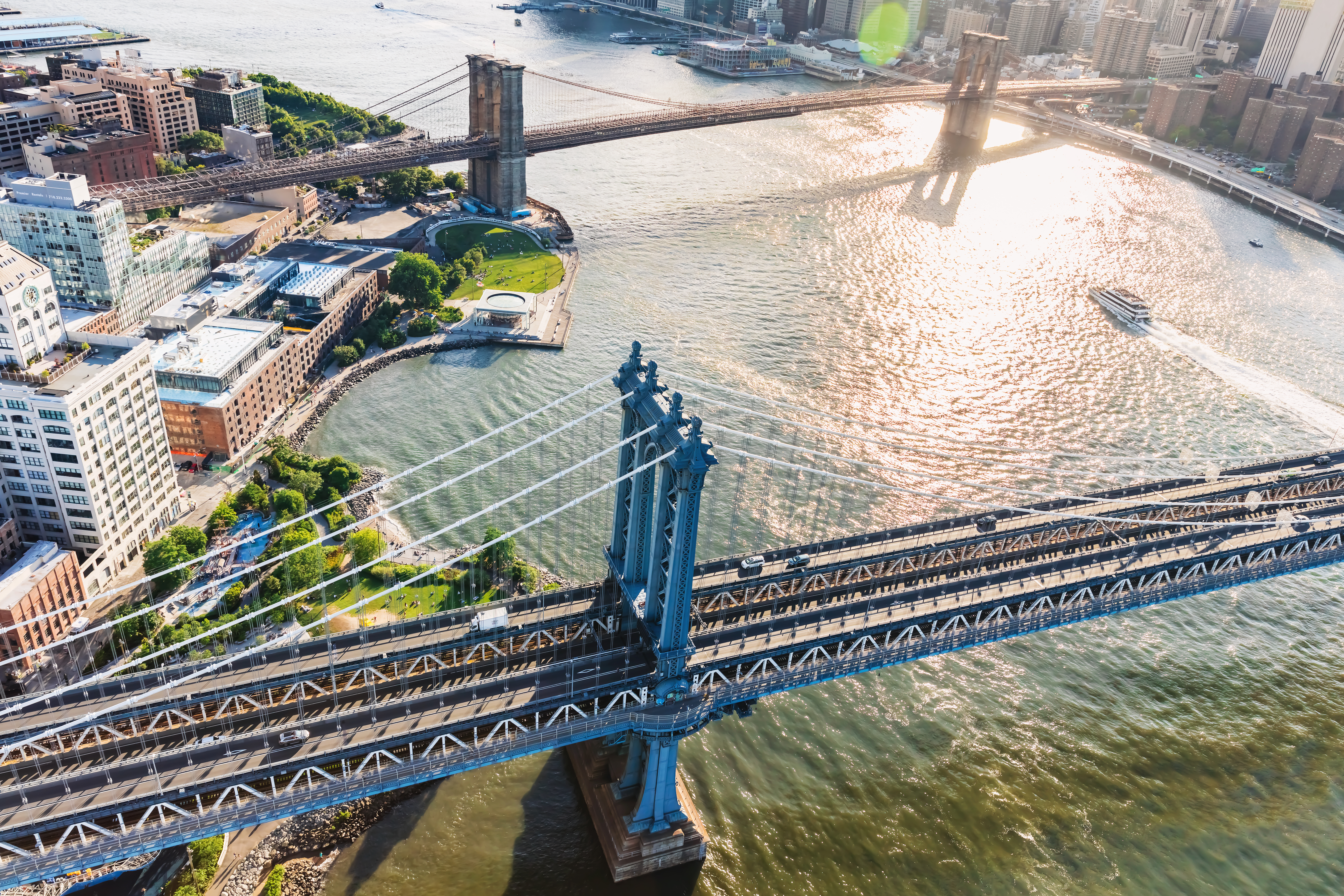 An areal shot of the East River with two bridges spanning across it.