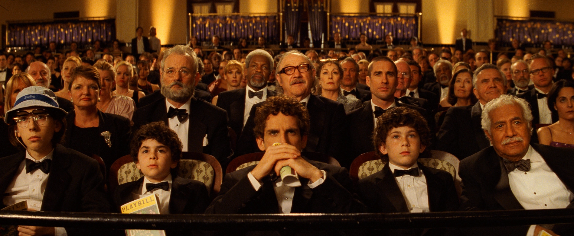 the cast of the royal tennebaums sits in the balcony of a theater