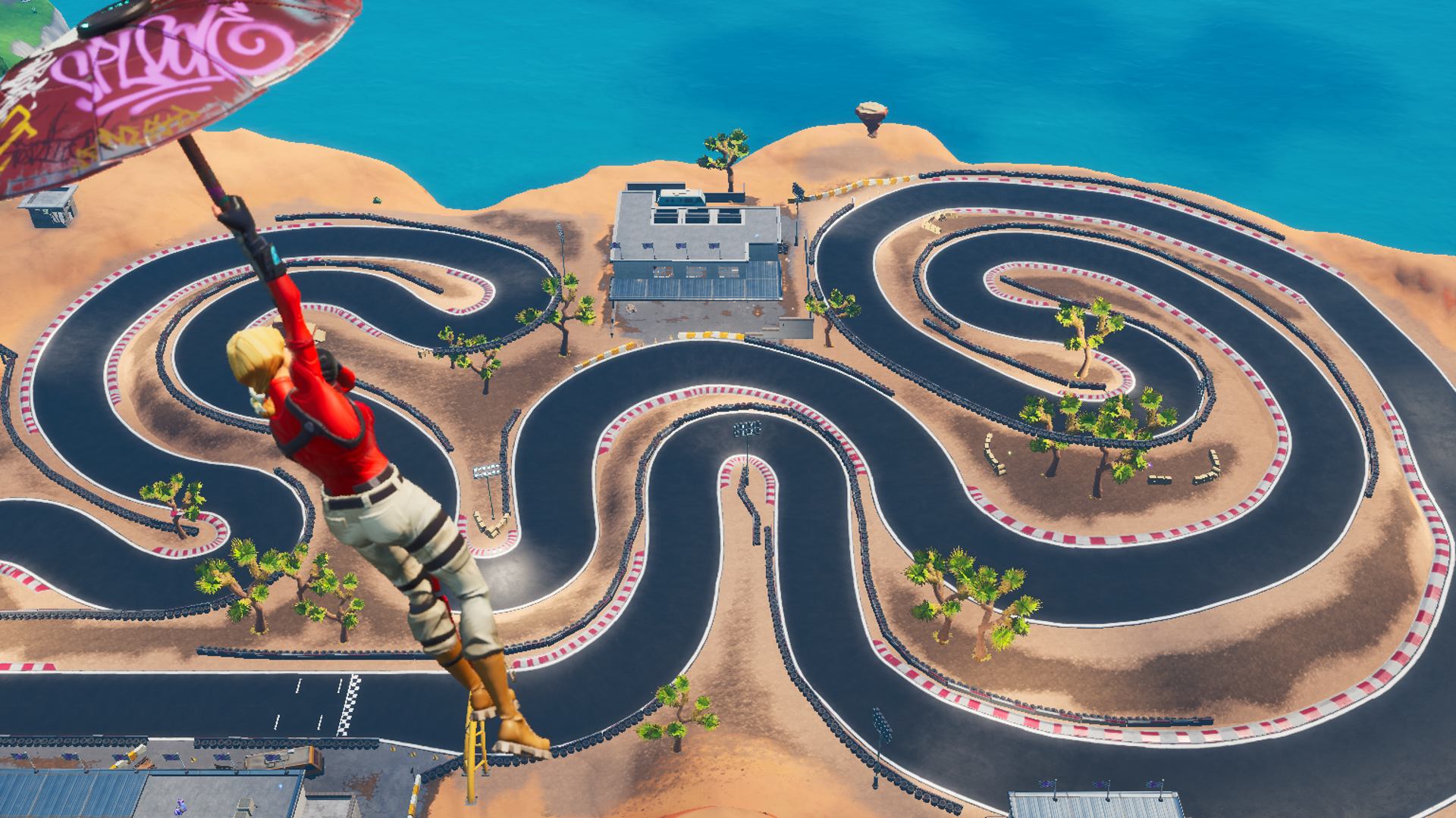A Fortnite player glides toward a racetrack in the desert