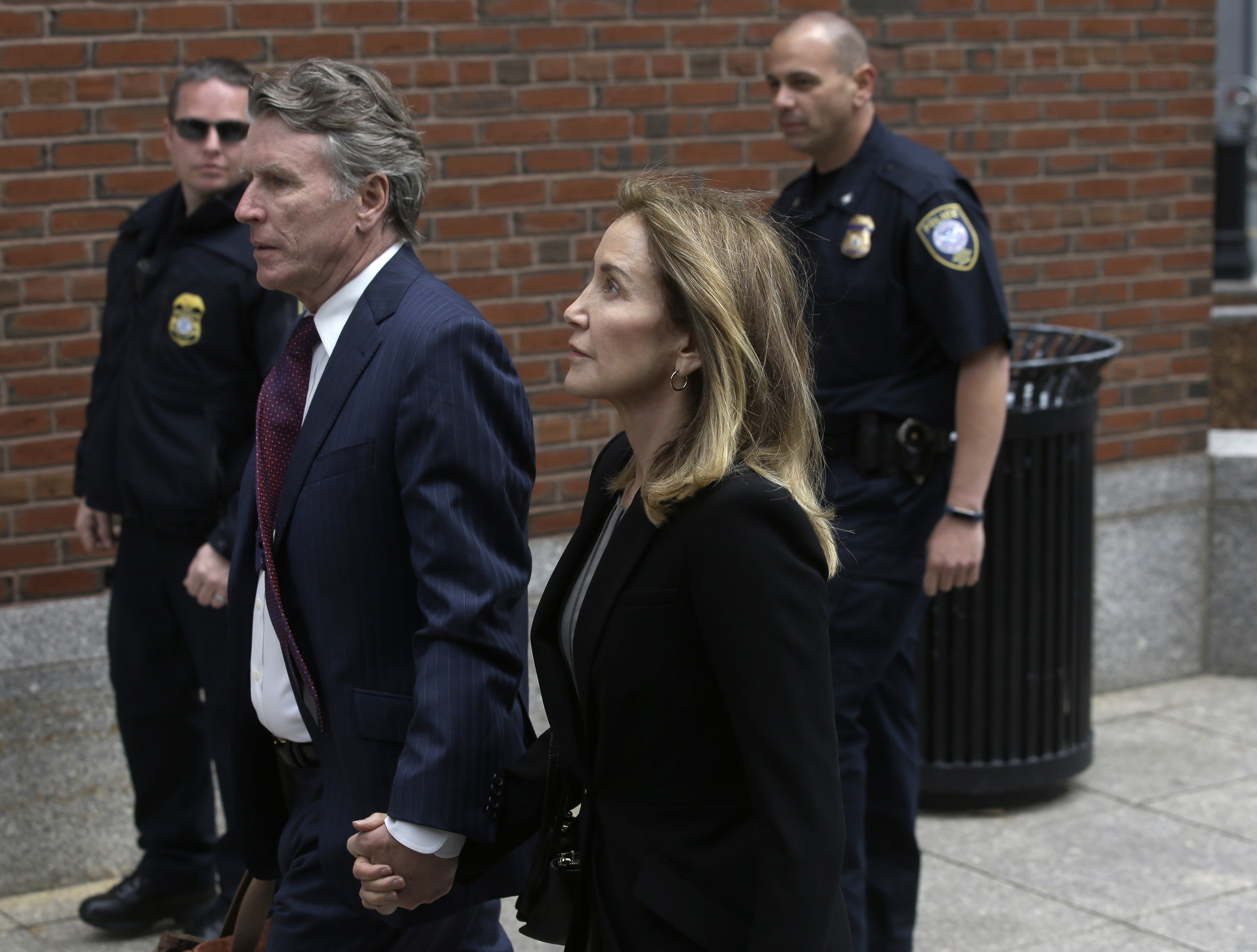 Actress Felicity Huffman arrives with her brother Moore Huffman Jr., at federal court Monday, May 13, 2019, in Boston, where she is scheduled to plead guilty to charges in a nationwide college admissions bribery scandal.