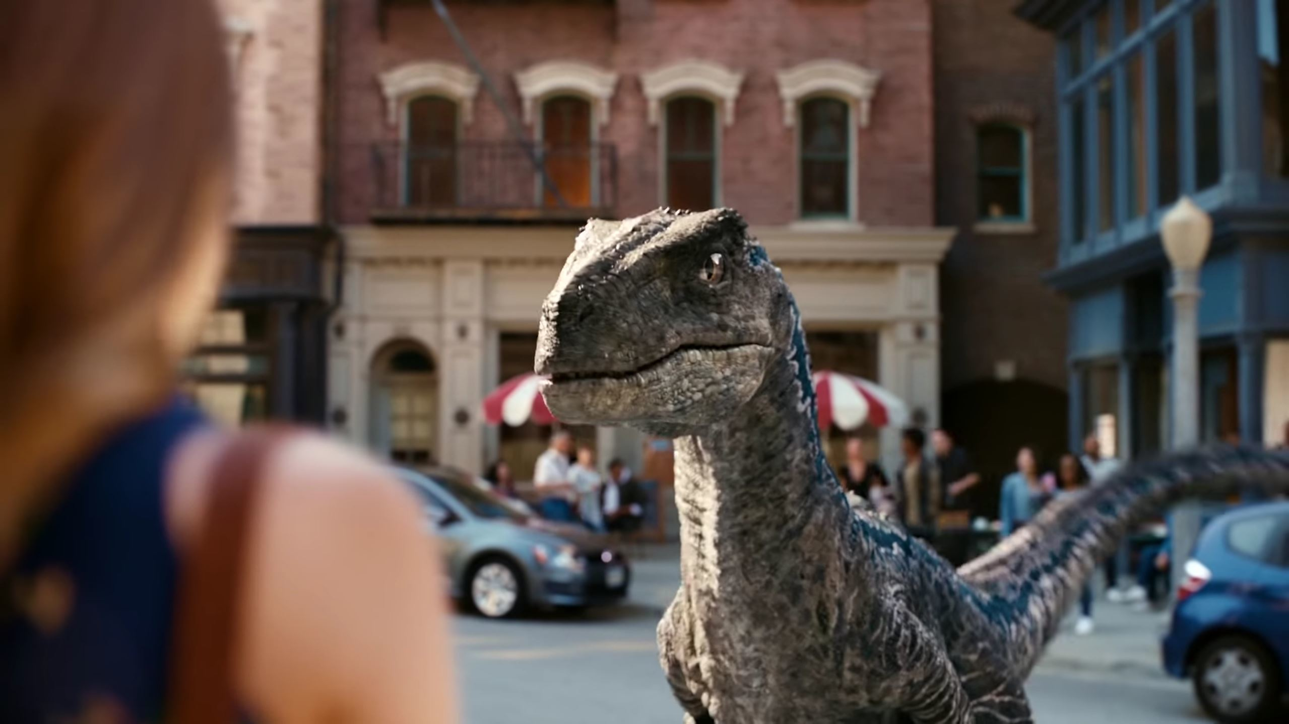 A velociraptor stares down a shopper in an urban setting in the live-action advertisement for Jurassic World Alive.