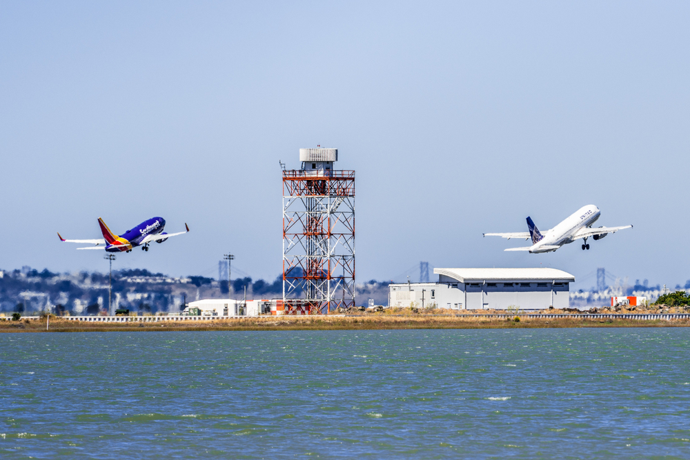 Two planes taking off from the San Francisco International Airport, with a tower visible between them.