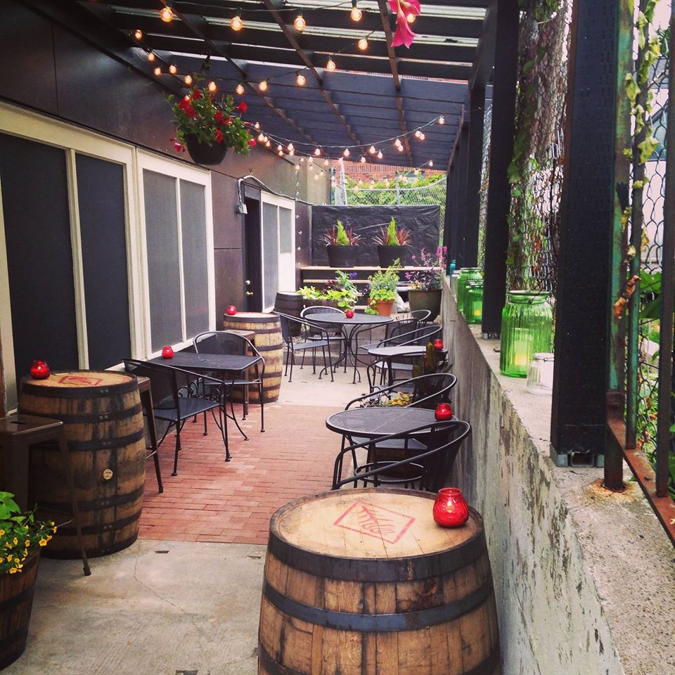 The side patio at 418 Public House, with string lights and cafe tables.